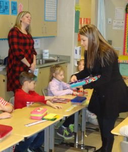 Kara Kasula, representing Nick Strimbu Inc., hands out books to students in Kendra Opperman's first-grade class at Brookfield Elementary School.