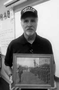 "Patrick T. Gleason holds a photo of himself from his days as a member of the 82nd Airborne, based in Fort Bragg, N.C. Gleason, a substitute teacher in local schools, served from 1966-70 in the U.S. Army, including a year in Vietnam. Eighth-grade teachers Melanie Horn and Miriam Necastro are teaching the book ""Inside Out and Back Again"" in class, a tale of South Vietnamese who become refugees after the fall of Saigon. Gleason talked about his experiences in the country, showing photos of his battalion and his uniform."