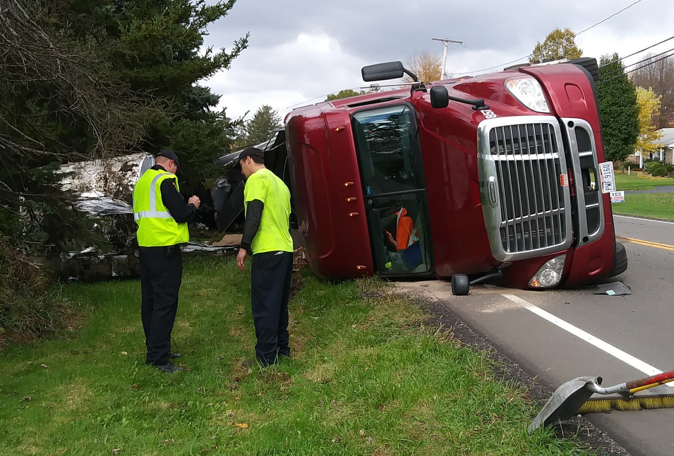 Truck driver Tyler Reichwein, right, talks to an Ohio Highway Patrol inspector after this crash on Route 7.