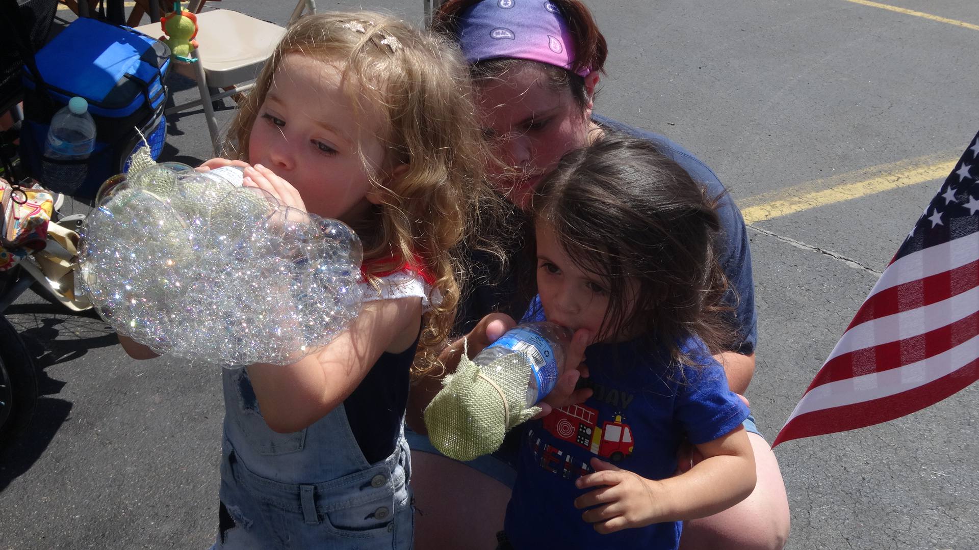 Brittany Williams helps her niece, Bailee, 3, and daughter, Gabriella, 2, blow bubbles,
