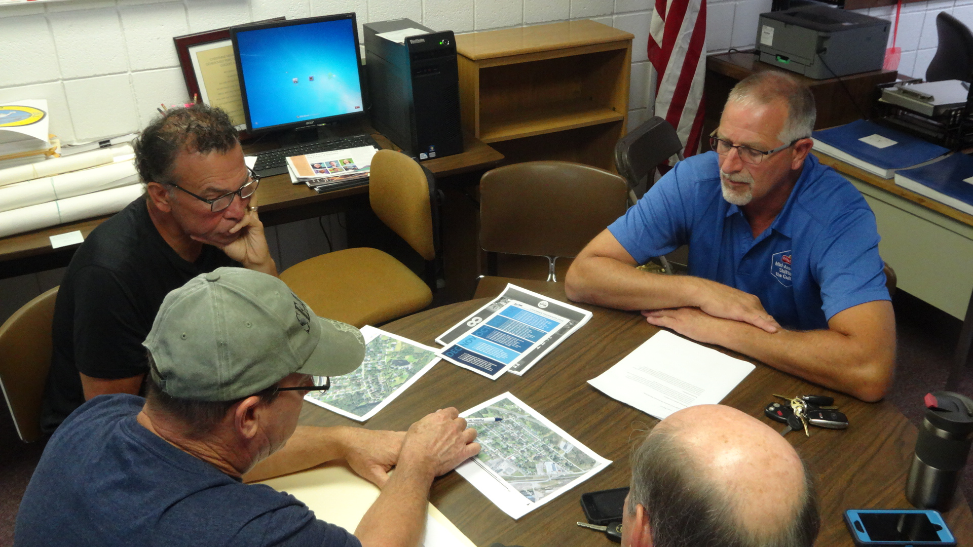 Brookfield Road Superintendent Jaime Fredenburg, in hat, points to a map to show an area that floods in the Valley View neighborhood. Also shown are, clockwise from left, resident Steve Franz and Trustees Ron Haun and Gary Lees.
