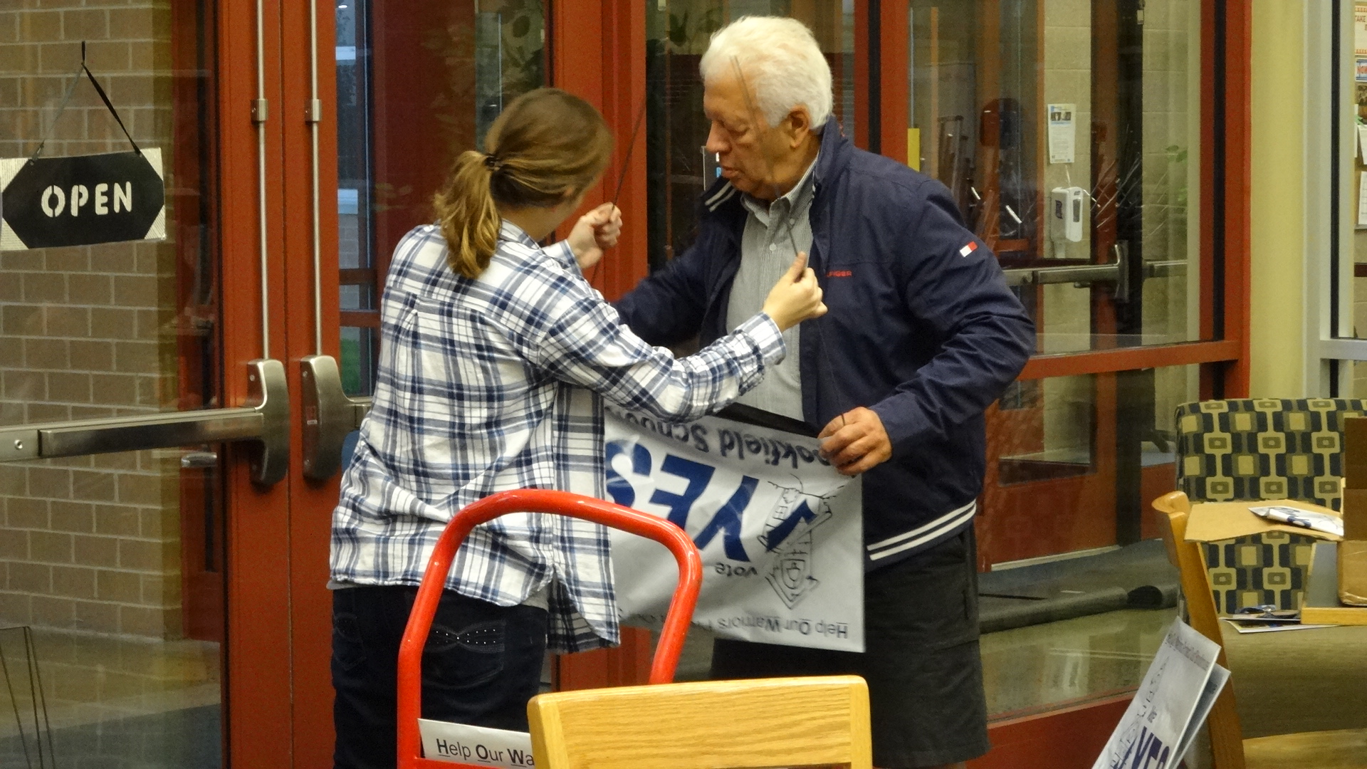 Brookfield Middle School eighth-grade teacher Marissa Miller and Brookfield Board of Education member George Economides assemble a sign promoting the school's request for a permanent improvement levy.