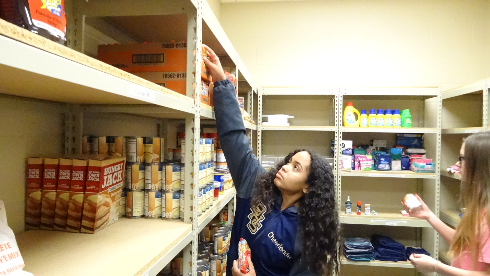 Seantya Brown stocks the food pantry at Brookfield Middle School. The pantry, which is open to high school students as well, also stocks hygiene and personal care items and clothing.