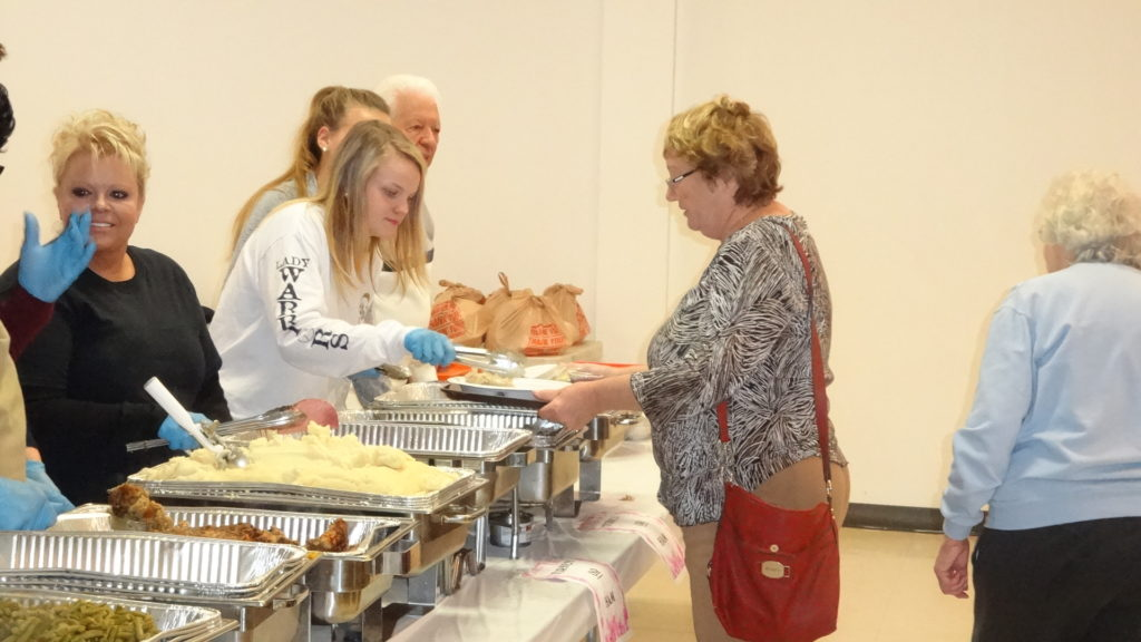 Brookfield High School senior Julianne First serves former teacher Marsha Jones at Brookfield Township Outreach Association's annual free community Thanksgiving dinner.