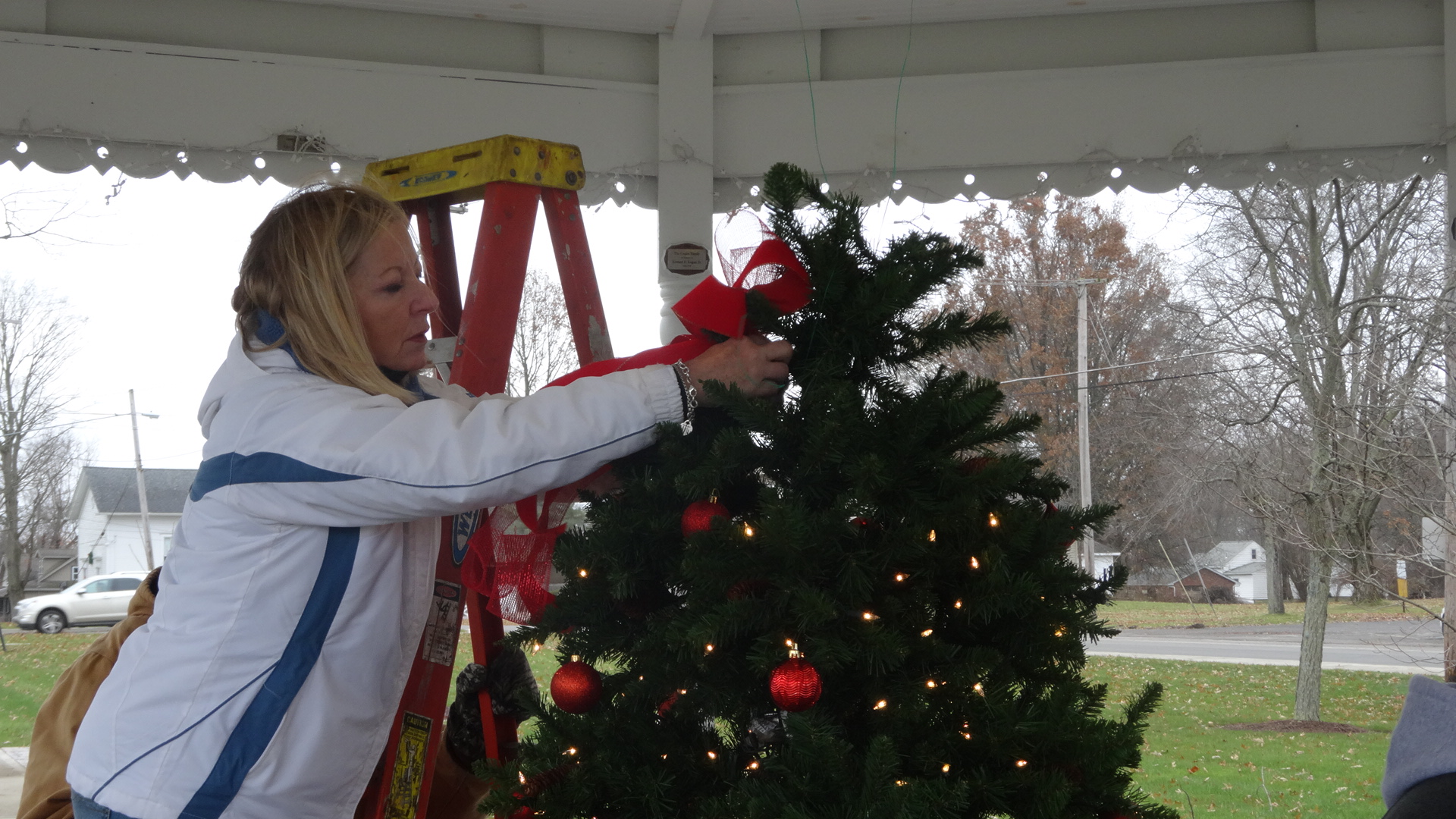Judy Pushcar pf the Brookfield Township Historical Commission decorates the Christmas tree in the gazebo on the green in Brookfield Center.