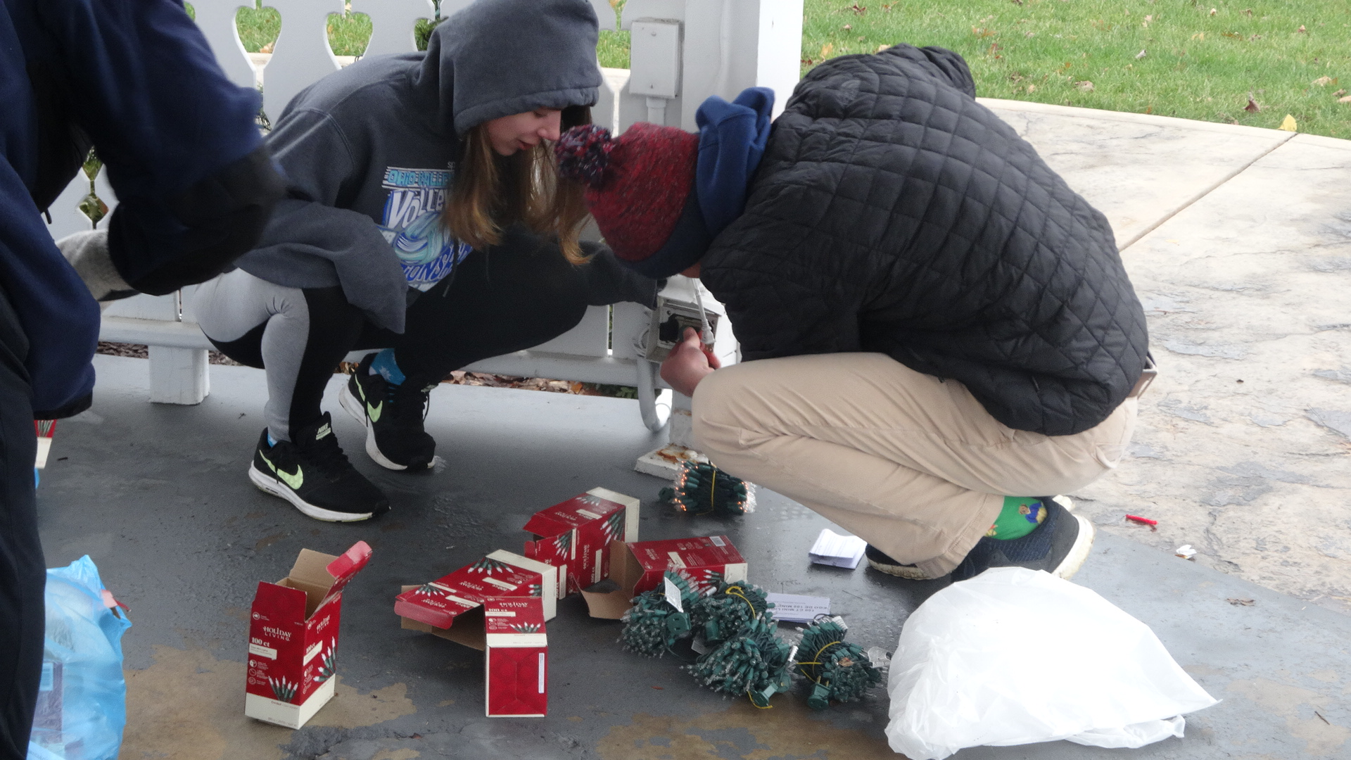 Nikole Husnick and T.J. Kirila of the Brookfield High School Interact Club check whether strings of lights work.