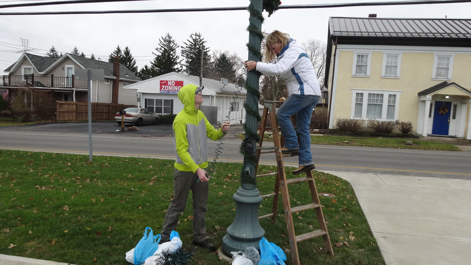 Ethan Karpinski of Hubbard helps Judy Pushcar of the Brookfield Township Historical Commission in wrapping lights and garland around a pole on the green in Brookfield Center.