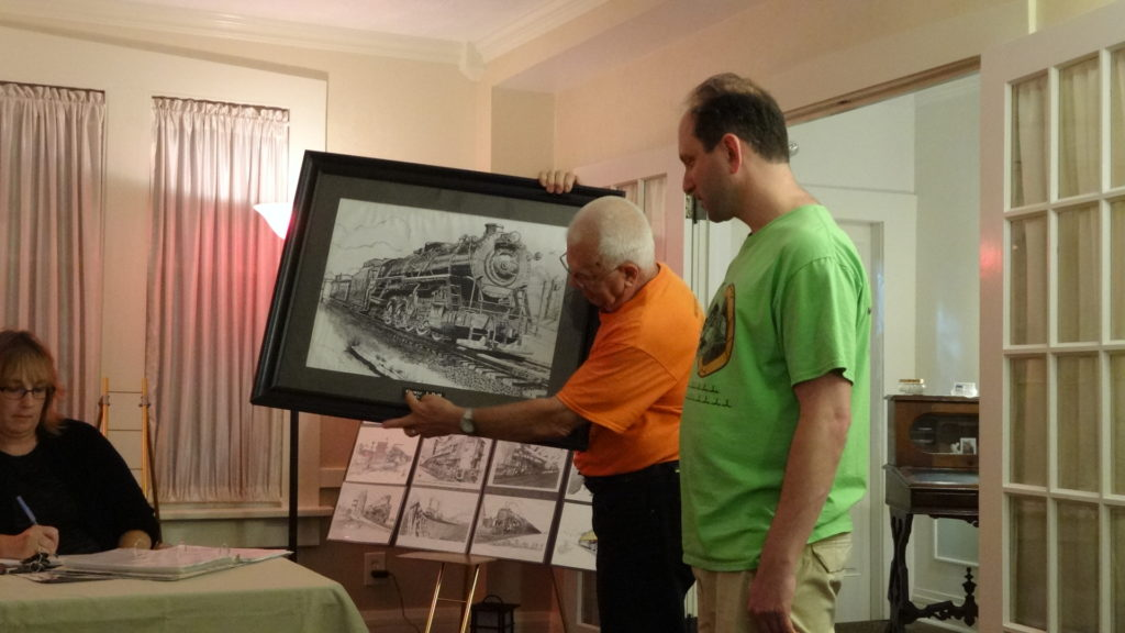 Ken Rogers, left, and Jonathan Richter of the Buhl Model Train Society donated this print of a George Dell drawing to the Brookfield Township Historical Society. Dawn Burns is at left.
