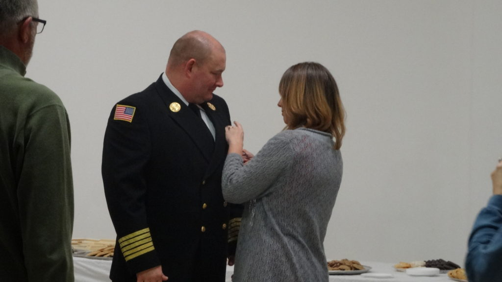 Holly Masirovits pins the Brookfield fire chief badge on her husband, David.