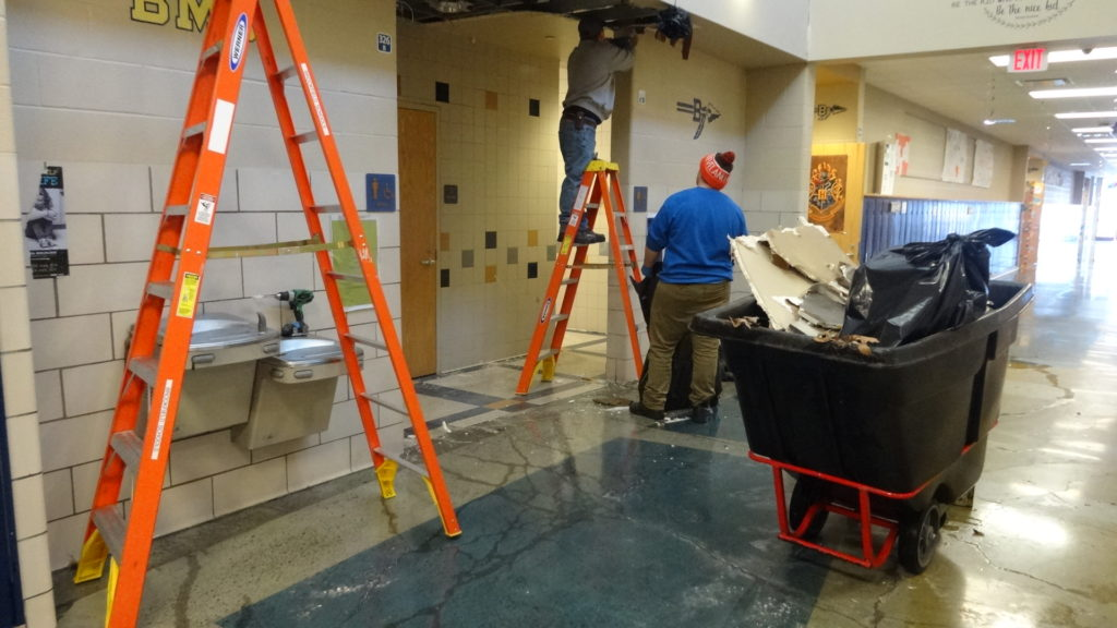 Ripping out wet ceiling tiles outside the Brookfield Middle School bathroom.