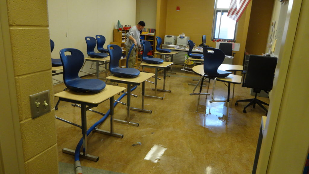 Buddy McClung of Disaster Recovery Services cleans up water in a classroom at Brookfield Middle School.
