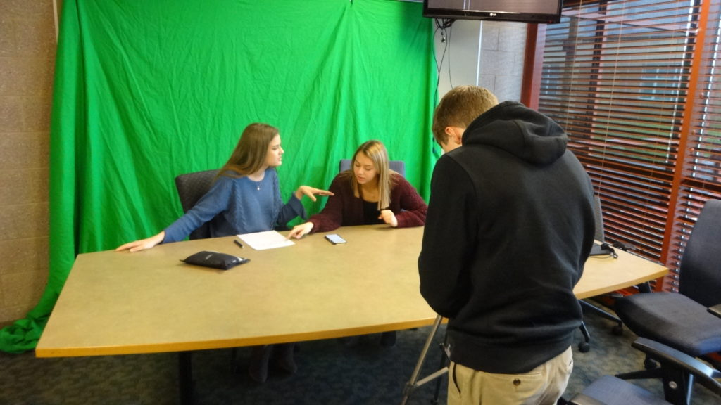 Ricky Atkinson lines up a shot while Stevie Olek, left, and Kayla Johnson go over the script for a WBHS newscast.