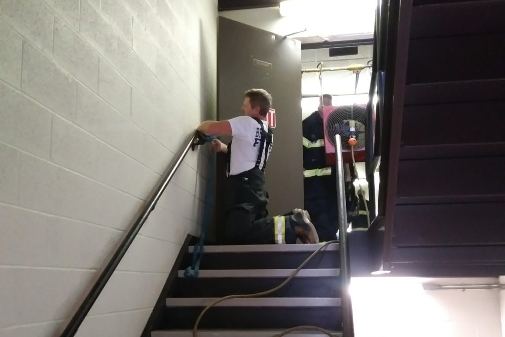 Dave Coffy ties open a door to air out an apartment complex after a cooking mishap in September.