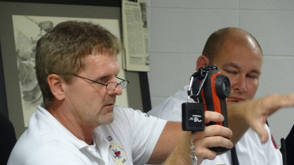 Dave Coffy holds a thermal imaging camera donated by the Brookfield Fallen Firefighters Foundation in October. Fire Chief David Masirovits is at right.