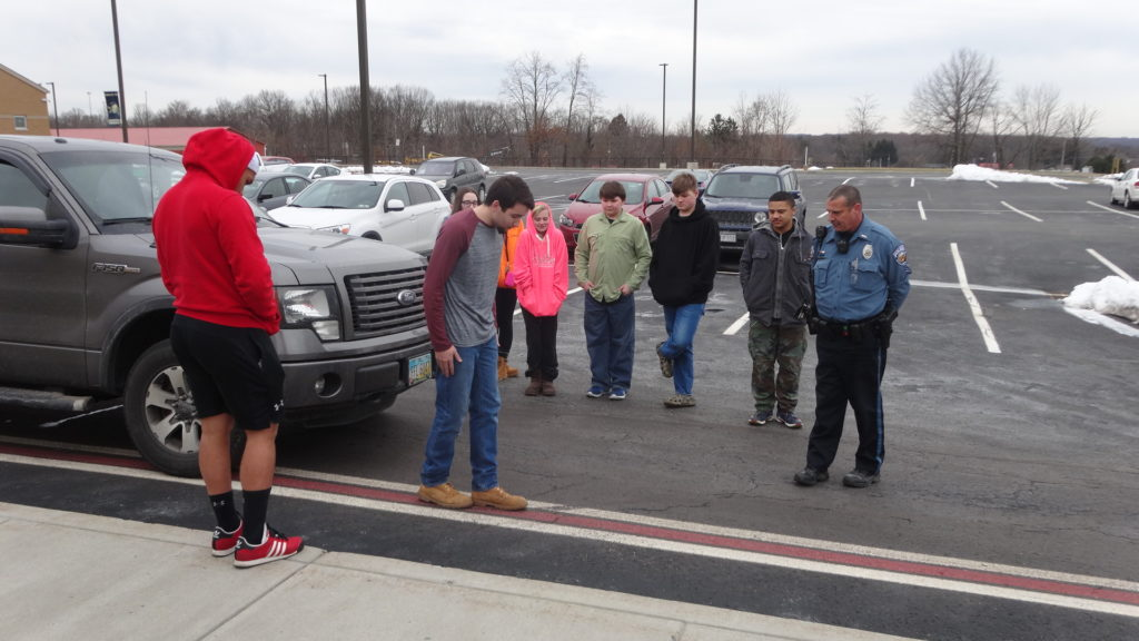 Brookfield High School senior Mike Evans walks the line during a mock field sobriety test under the eye of police Cpl. Ron Mann during a Brookfield Junior Police Academy session. The program concluded April 4.