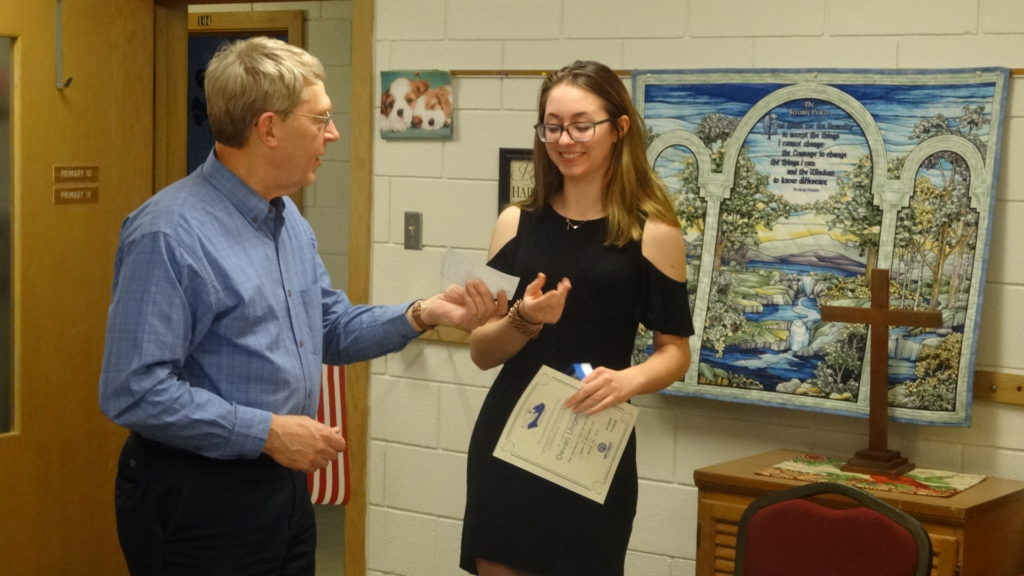 Brookfield Optimist Club member James Hoffman III presents Brookfield High School junior Devan Ungerer with a $100 check for winning first place in the club's essay contest.