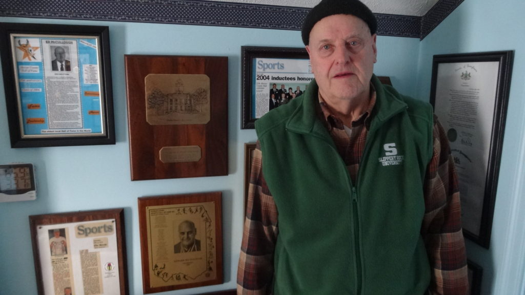 Ed McCullough stands next to plaques he received when he was inducted into the Mercer County Hall of Fame and the Pennsylvania Sports Hall of Fame.