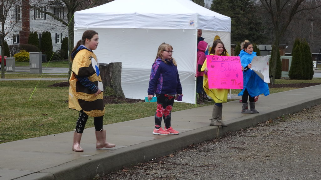 Girl Scouts, from left, Aeryn Berena, Caitlyn McGinnis, Kaylin Jones and Madison Obermeiyer try to get motorists to stop at a drive-up cookie sale booth on the green in Brookfield.