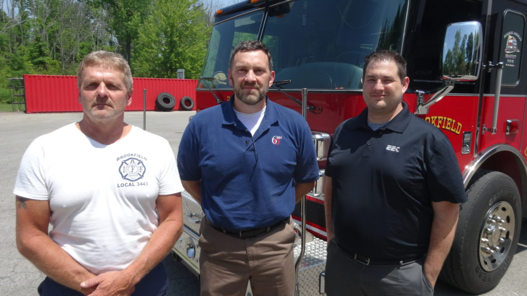 Dave Coffy, left, stands with Pat Callihan, center, and Hank Stull of Ellwood Engineered Castings after the company donated $500 to the Brookfield Township Fire Department.