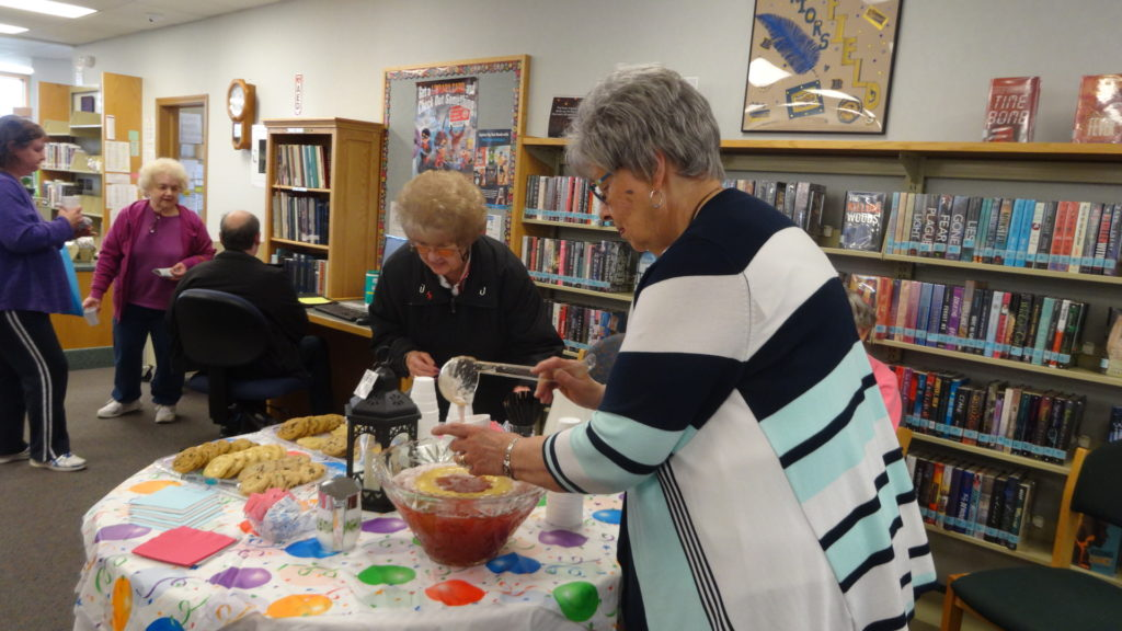 Friend of the Brookfield Library Nancy Herrmann, right, pours punch for Judy Klepfer, center, at a Brookfield Branch Library open house.