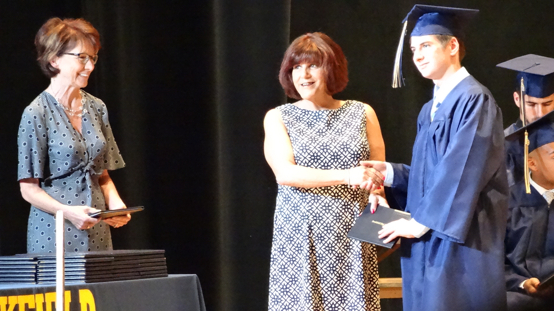Logan Moore accepts his diploma from Brookfield Board of Education President Ronad Bonekovic. Superintendent Velina Jo Taylor is at left.