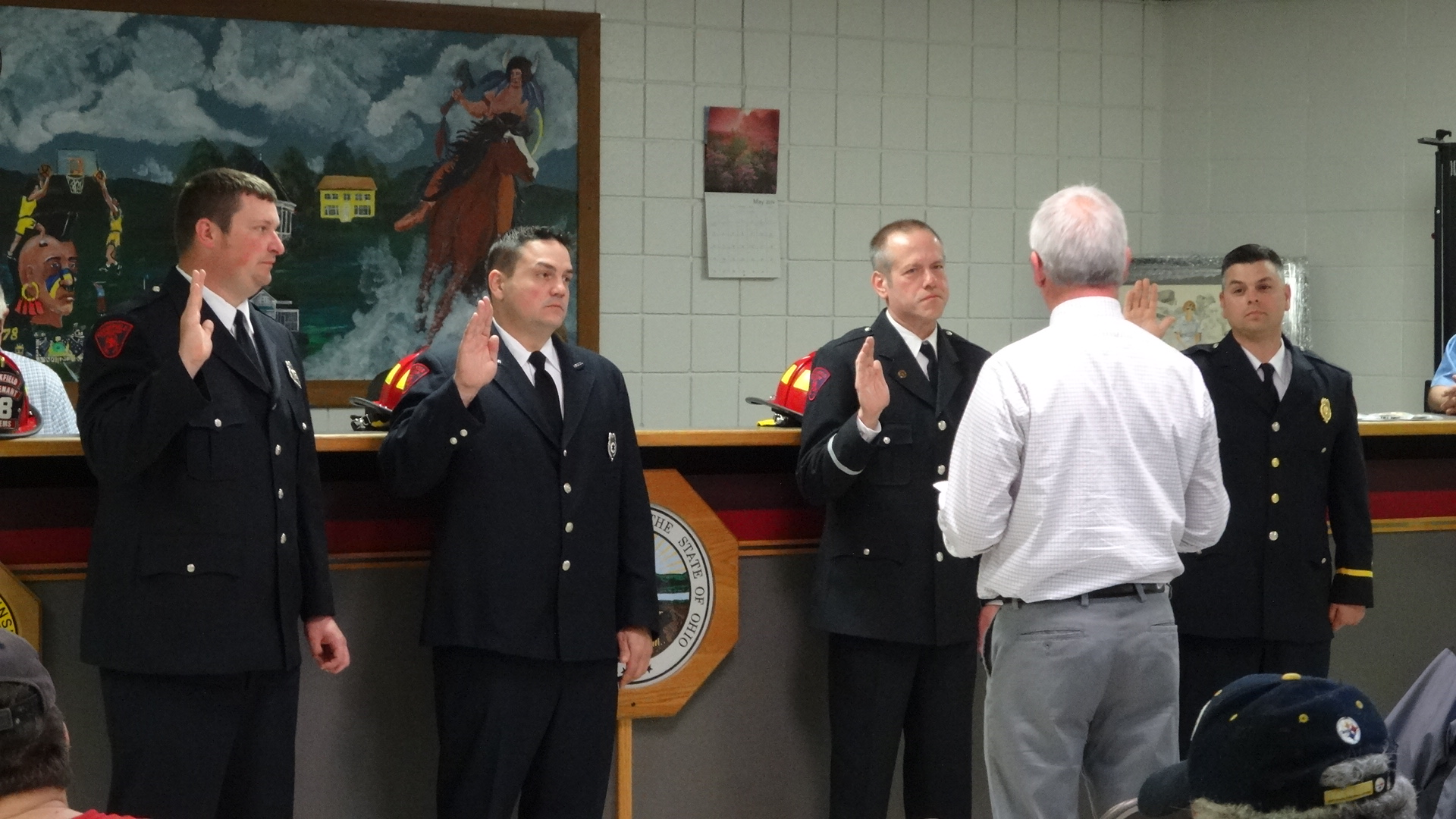 Brookfield Trustee Dan Suttles, whose back is to the camera, administers the oath to newly promoted firefighters, from left, career Lt. Steve Smoot, volunteer Capt. Randy Richman, volunteer Lt. Jim Richmond, and career Capt. Nick Cresanto.
