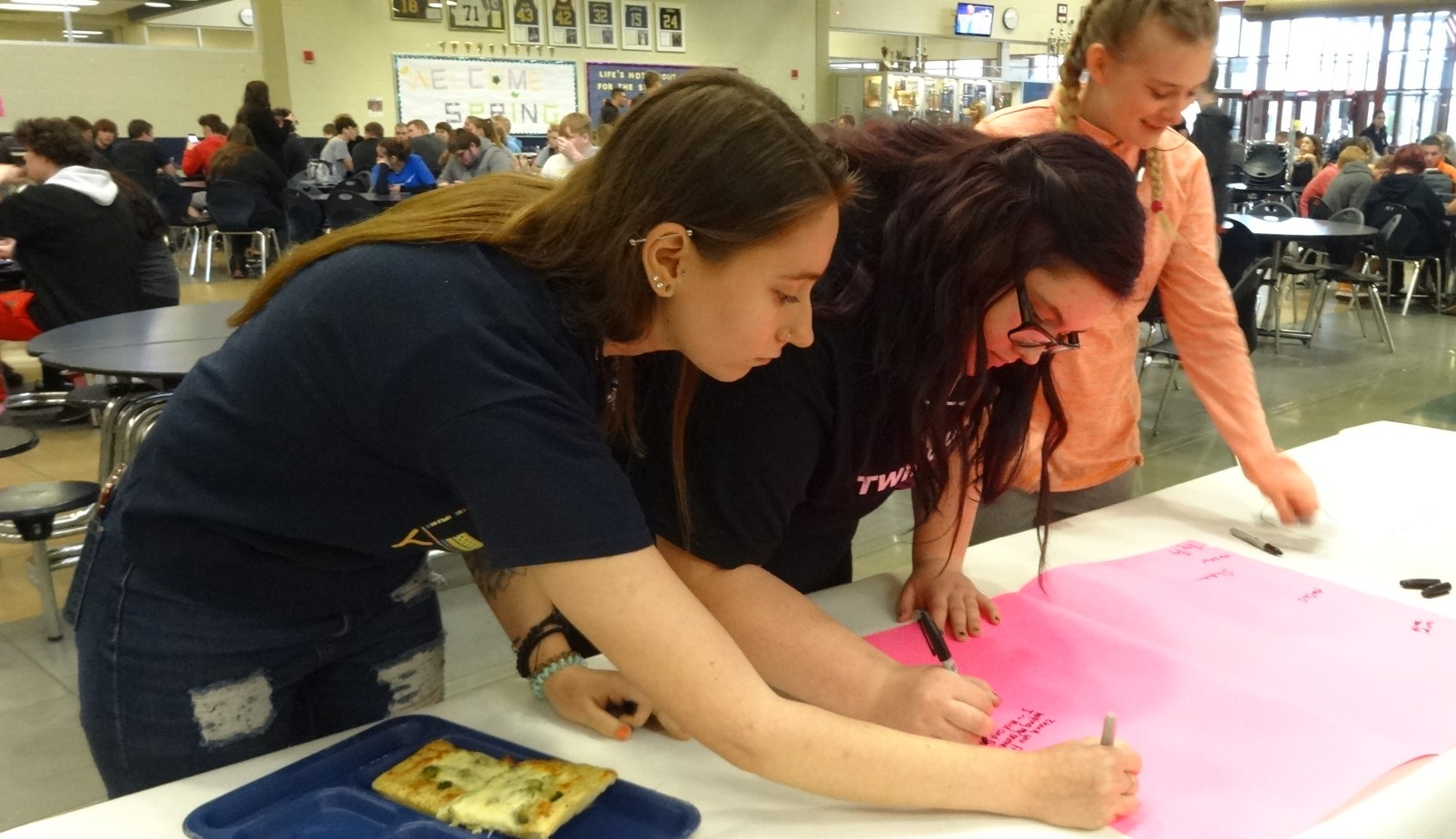Brookfield students, from left, Brena Dugan, Macey Devine and Kaytlyn Horton sign a card for the Brookfield Fallen Firefighters Association.