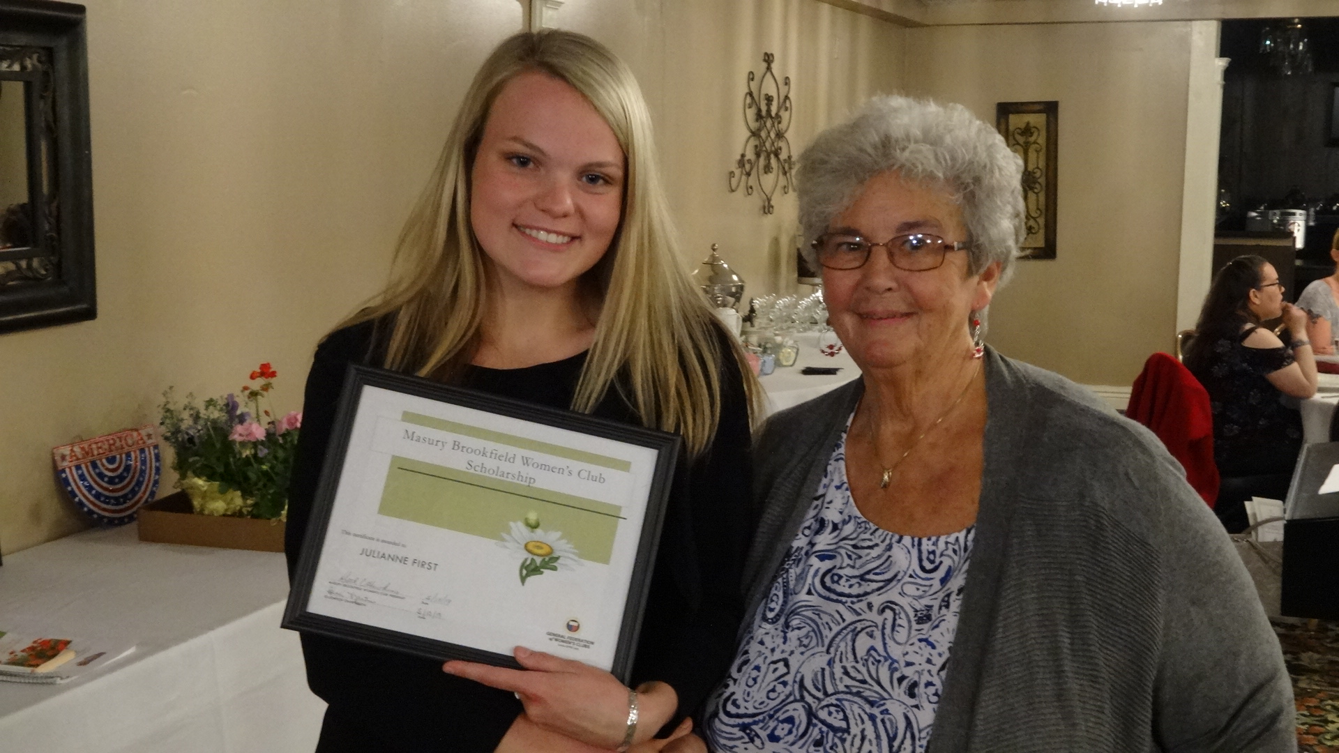 Brookfield High School senior Julianne First holds the certificate she received for winning the Masury-Brookfield Women's Club scholarship. She was introduced by Mary Schmidt, at right.
