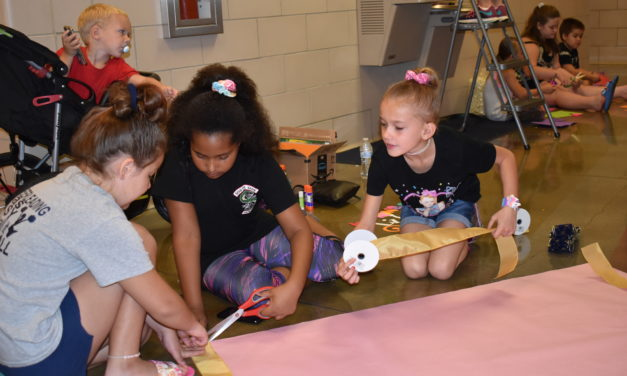 Cheerleaders lending a hand at school
