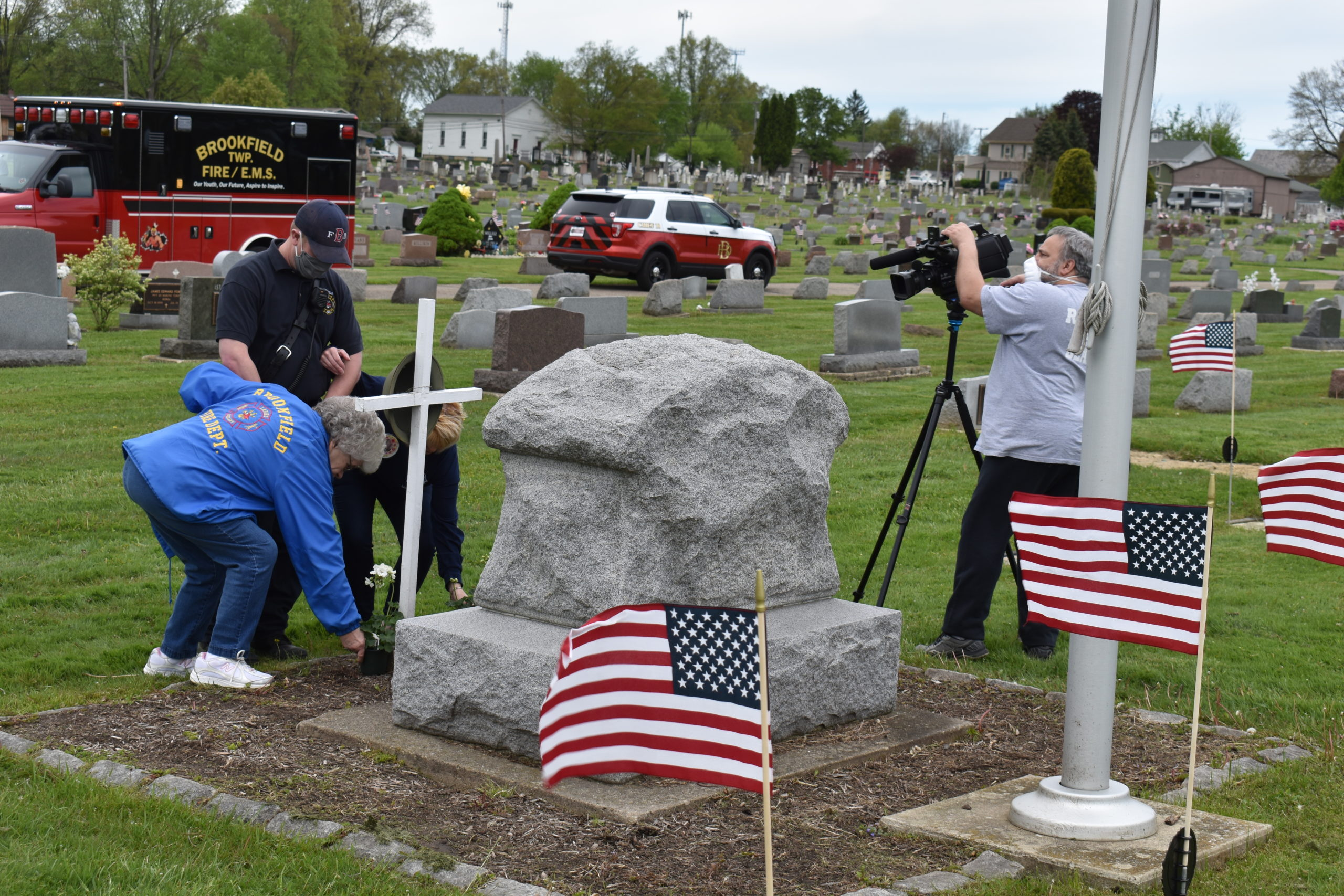 Pat Barnhart and Debbie Elliott, escorted by Russ Vereshack, place flowers on the veterans' marker in Brookfield Township Cemetery. Bob Vaia records the act for a video to be posted on the Brookfield Township Facebook page.
