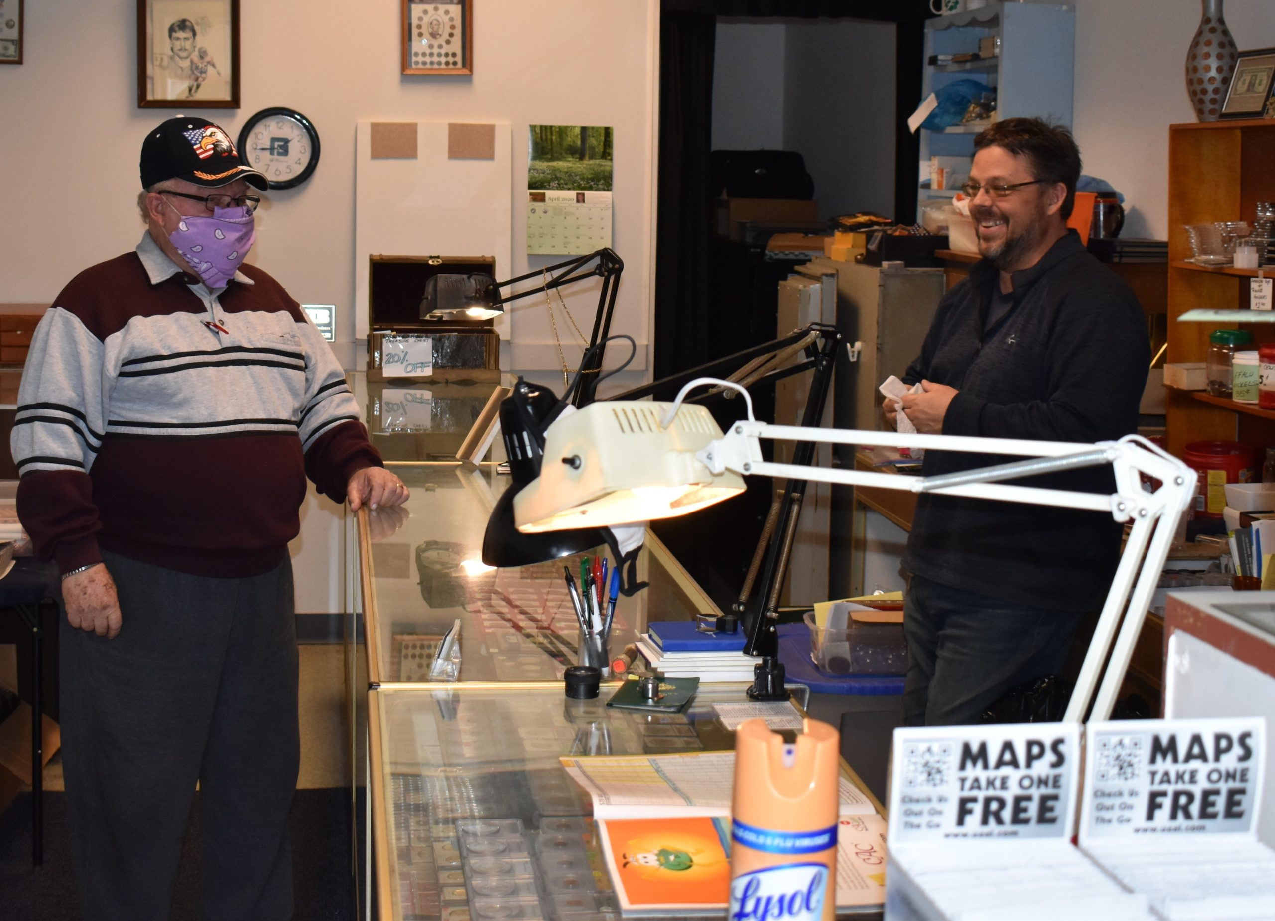 Miles Dotson, right, owner of Steel Valley Coin-N-Currency, Brookfield, chats with customer Hank Glogowski on May 1, the day Dotson reopened his store.