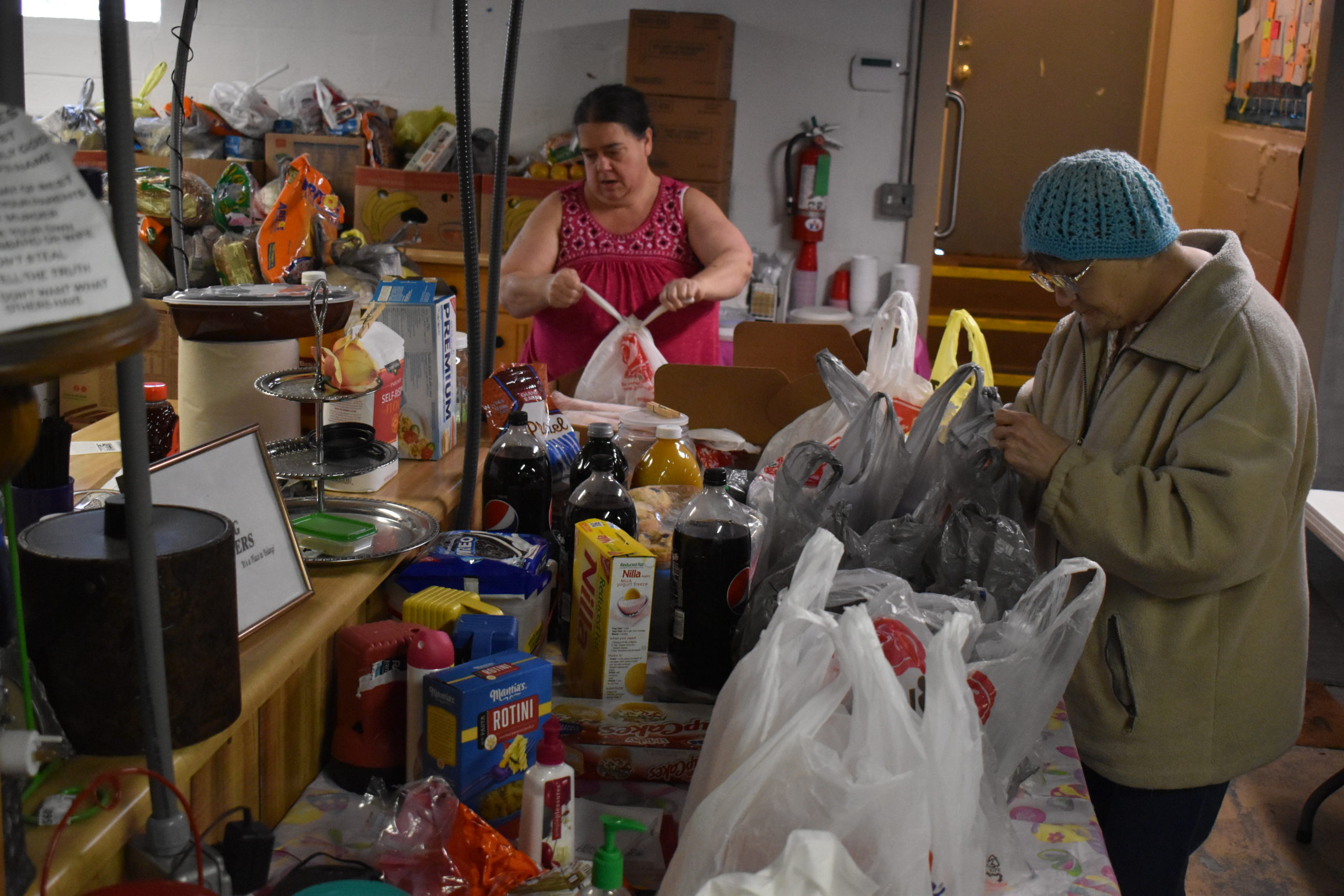 Mary McKelvey, left, and Maida Wilt load bags at the Salvation Army pantry at Living Waters Church, Brookfield.