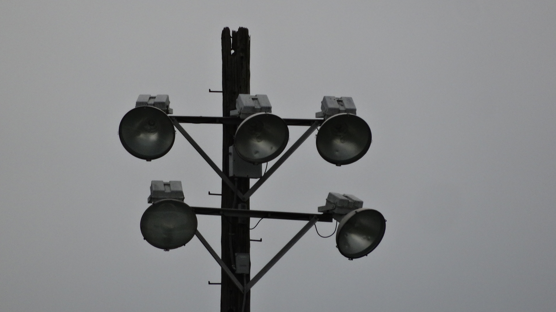 The frayed tops of the football stadium light poles show their age. The lights and poles are set to be replaced.