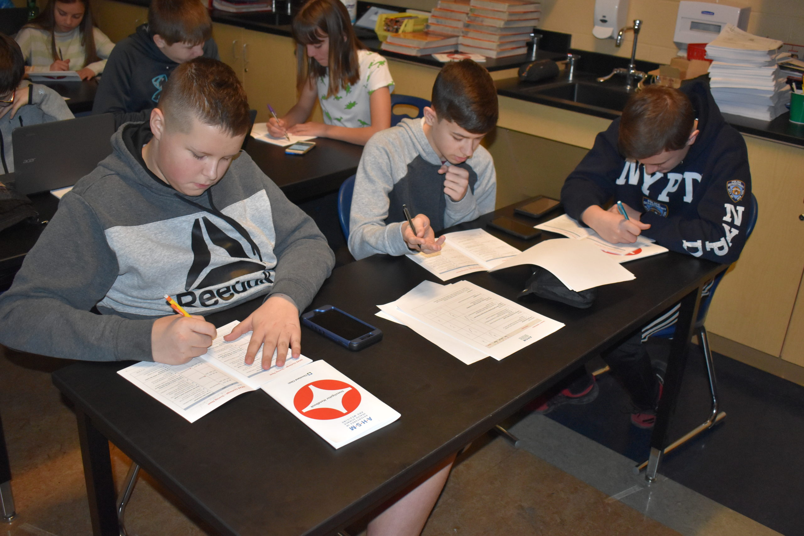 Brookfield eighth-grade students, from left, Hayden Hoskin, Anthony Rowe and Dallas Crozier write in their workbooks for Adventures in Health Science and Medicine, a program by the Cleveland Clinic.