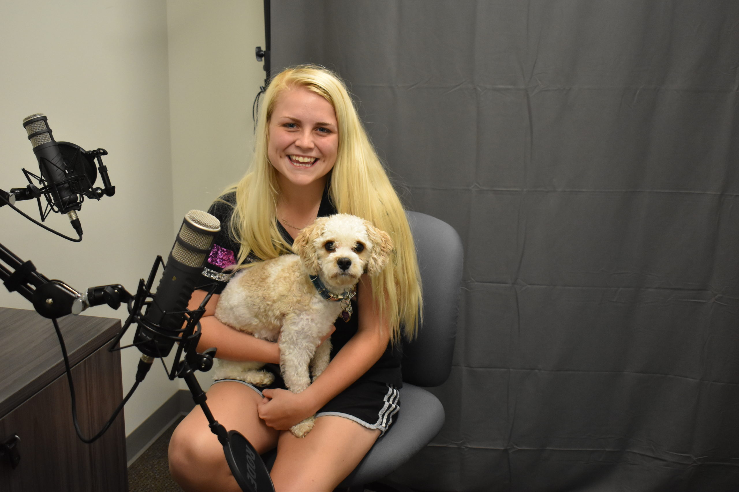 Reganne O'Brien and her dog, Thor, are shown in the podcast studio at the eCenter@LindenPointe in Hermitage.