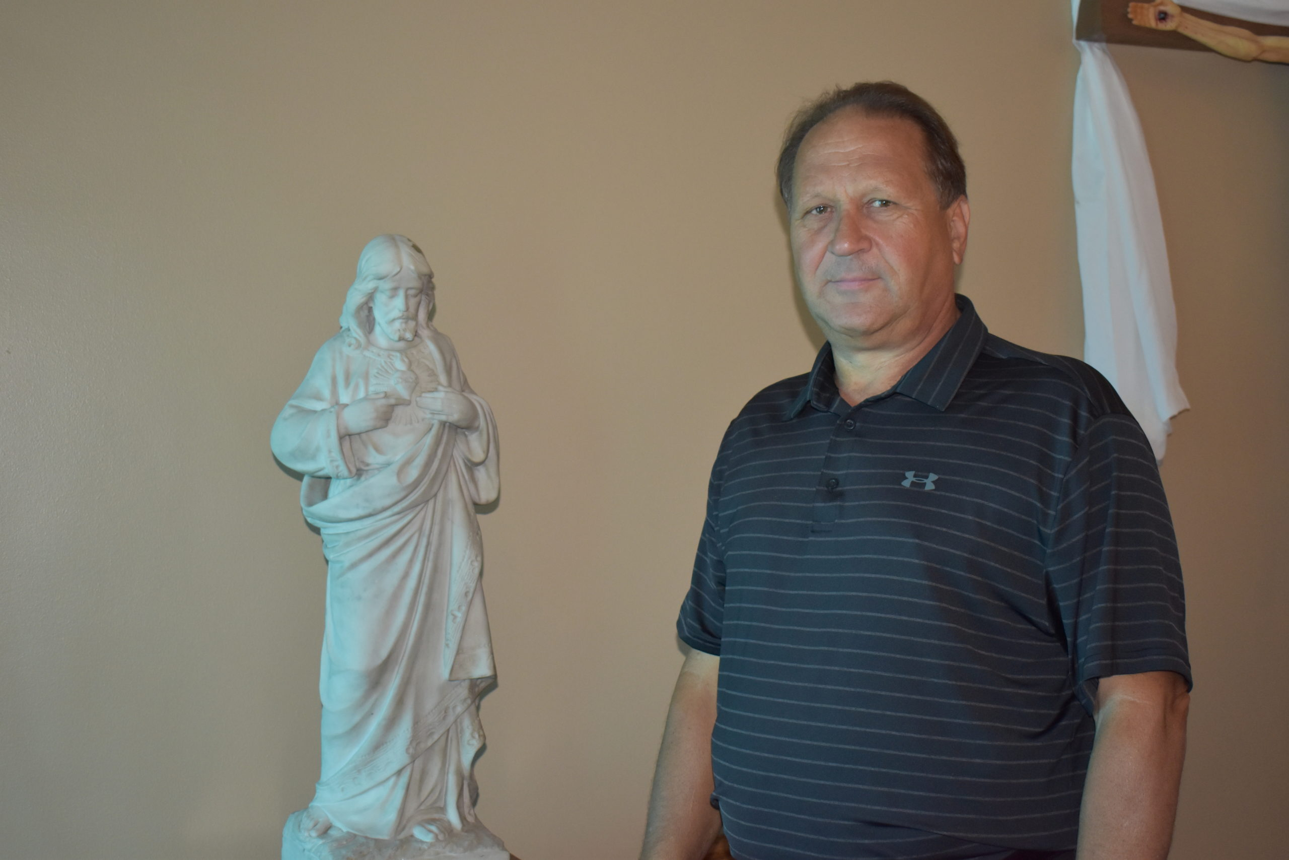 Mark Ferrara stands next to a statue of Jesus in the chapel of Kennedy Catholic High School. Ferrara has been named president of the Kennedy Catholic Family of Schools.