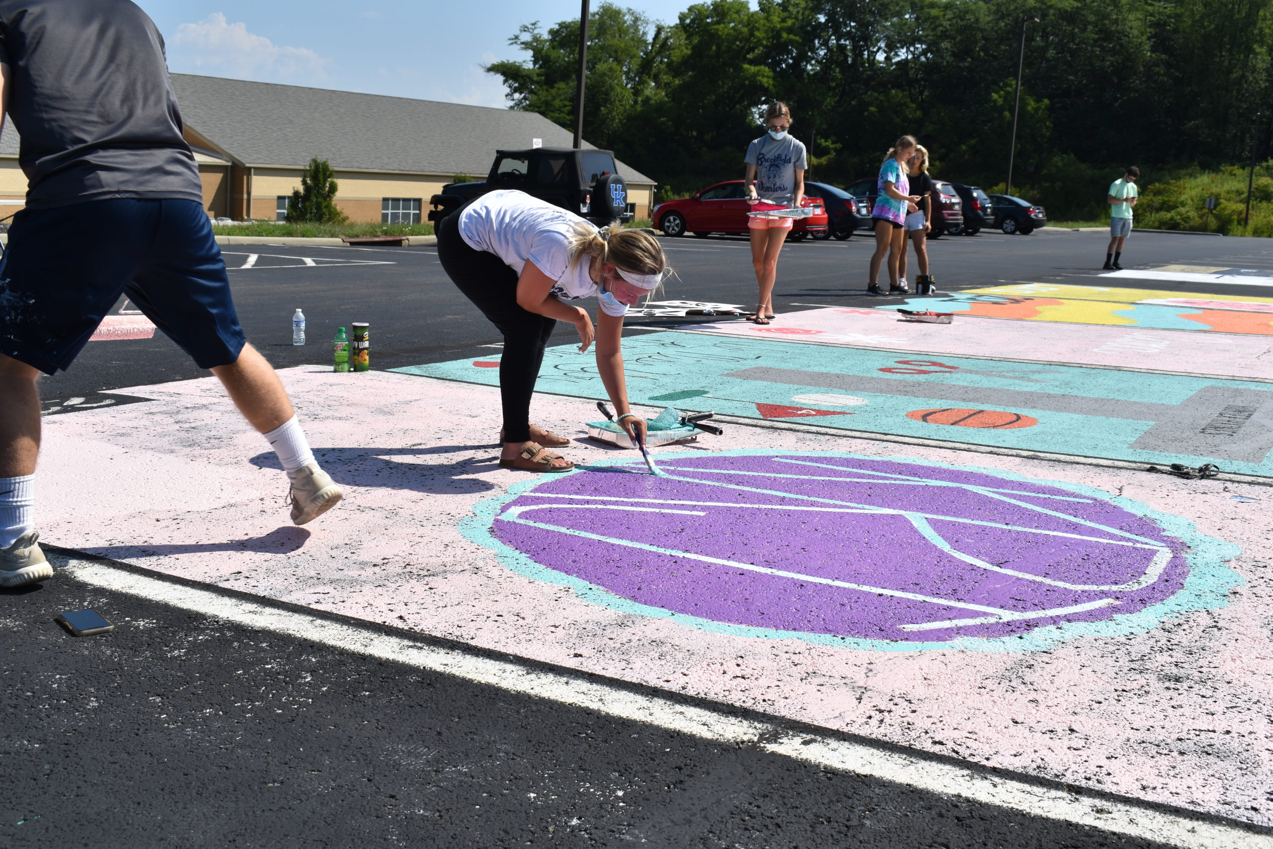 Kaelyn Johns, bending over, and other Brookfield High seniors paint their parking spaces in the school parking lot.