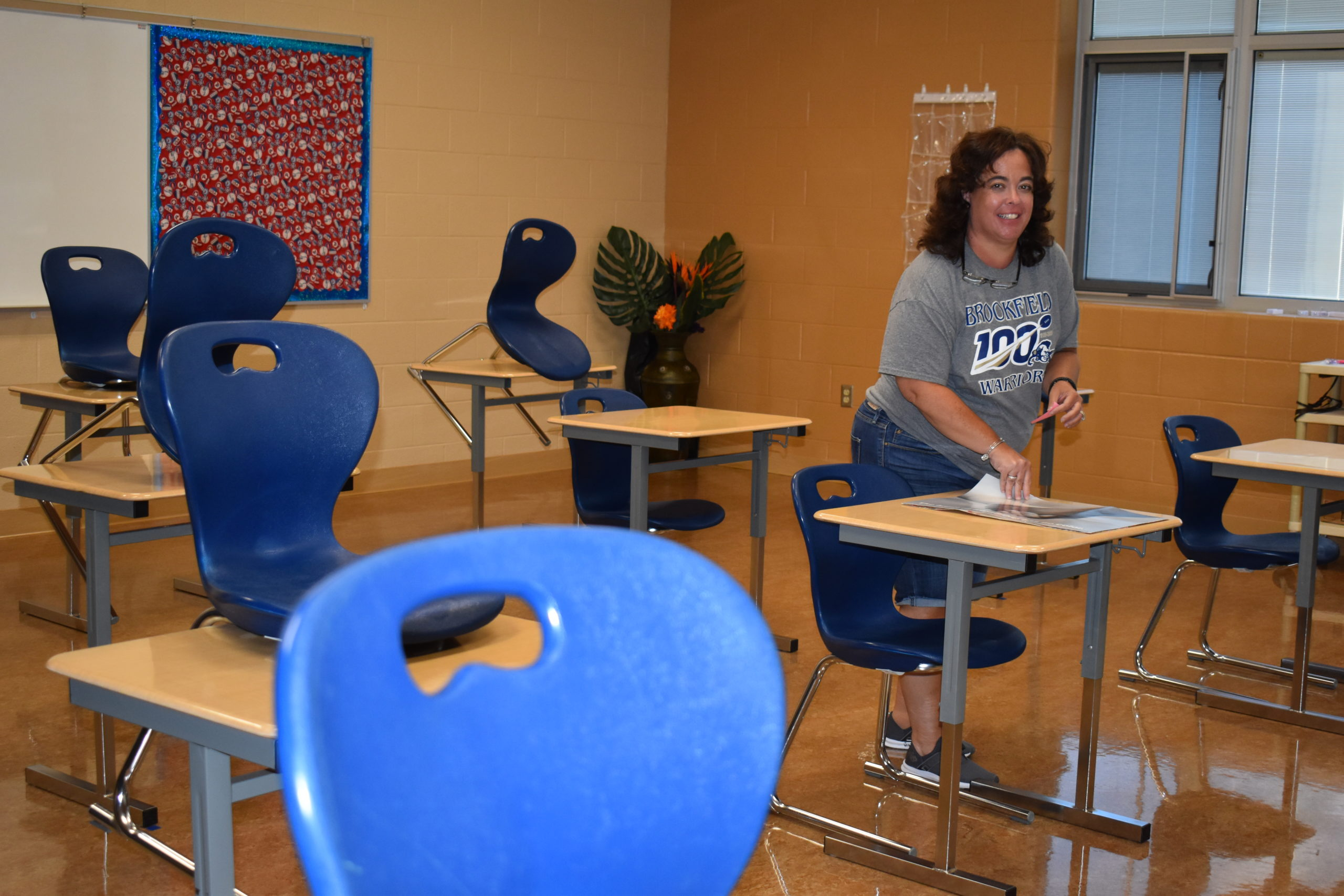 Brookfield High School teacher Mary Arp stands in her classroom showing the social distance arranging of desks. Typically, she has 28 desks in the room but health guidelines now permit no more than 15.