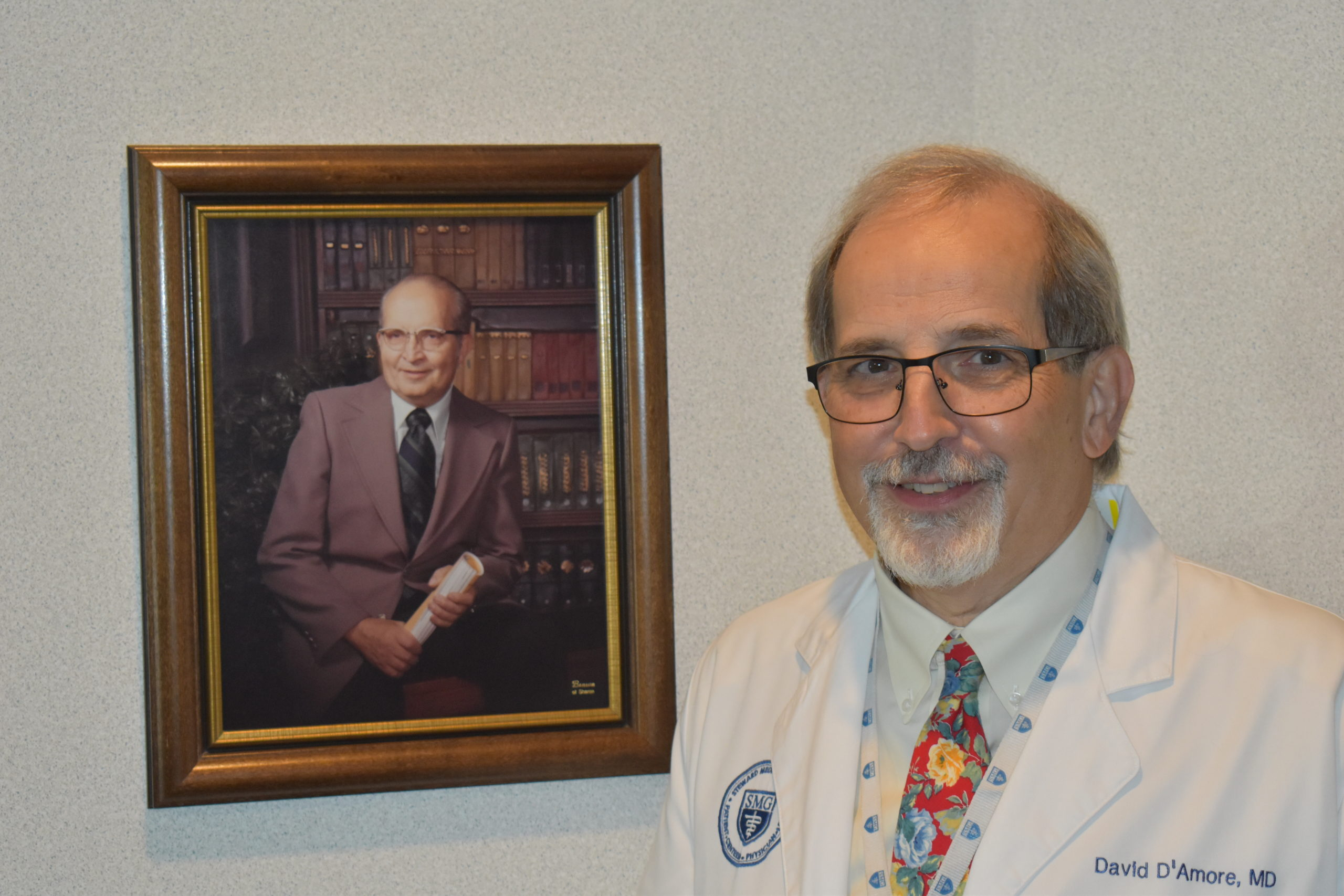Dr. David D'Amore, who this year marked 40 years practicing medicine, stands with a photo of his father, Dr. Amanto D'Amore, who practiced for 61 years.