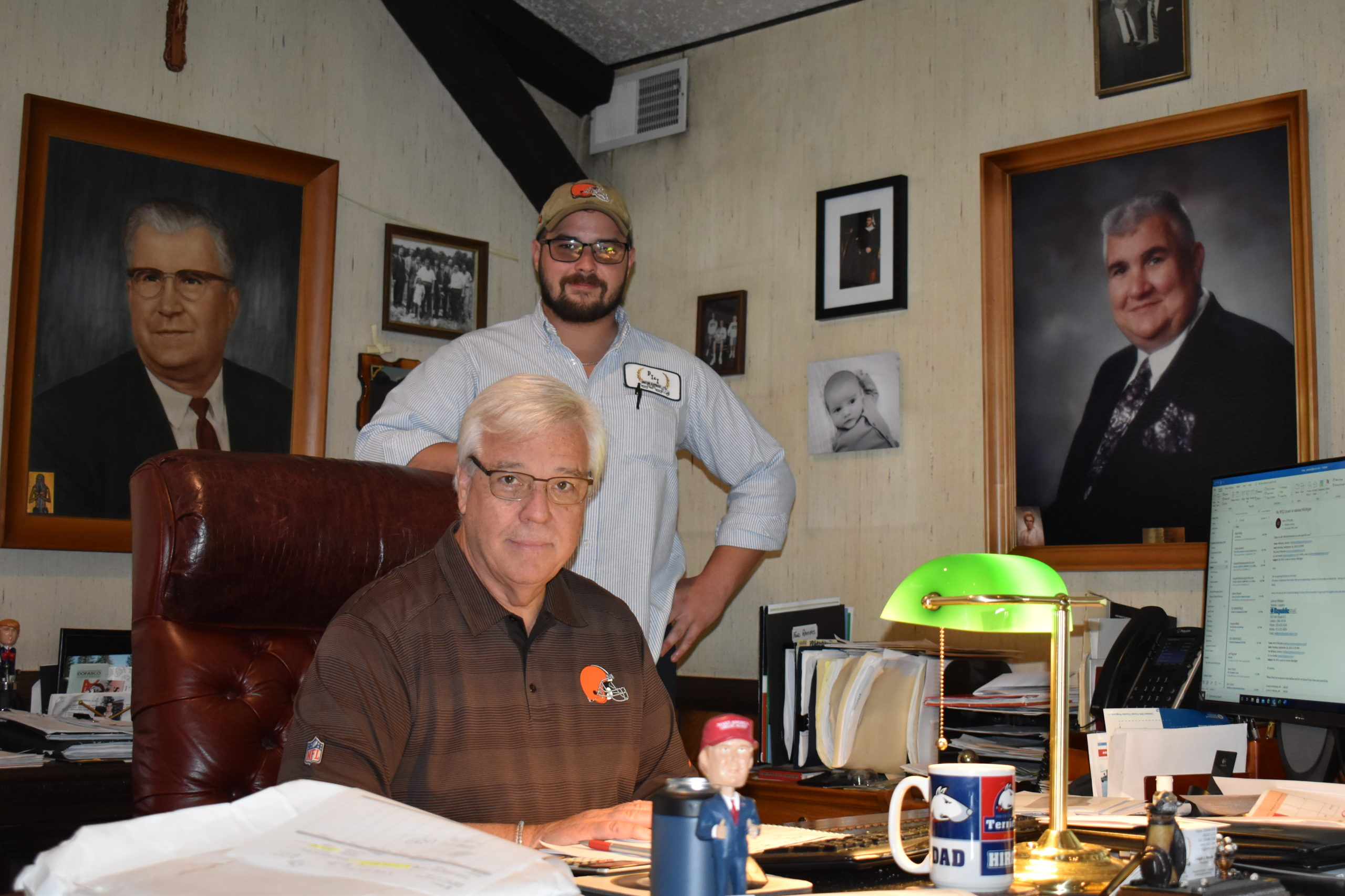 Joe Kerola, president and CEO of PI&I Motor Express, sits at his desk with his son, Jeremy, standing behind him. The picture at left is Kerola's grandfather, also named Joe, who founded the company, and at right is John Kerola, the current CEO's father.