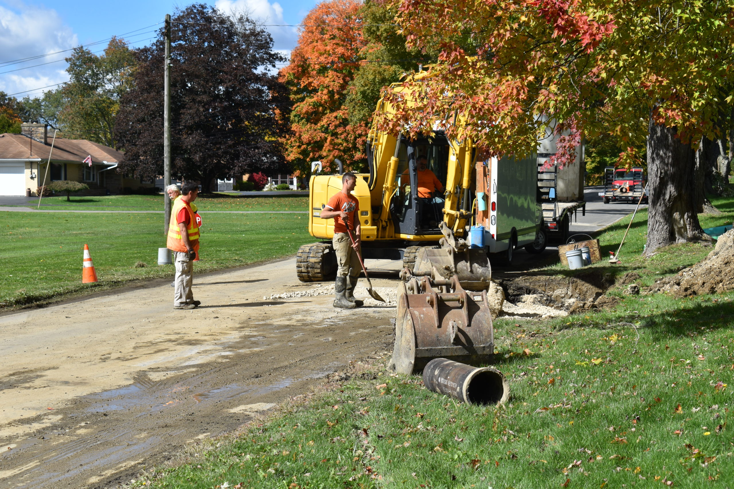 Trumbull County Water workers backfill the trench where a water main broke Oct. 8 on Yankee Run Road in Masury.