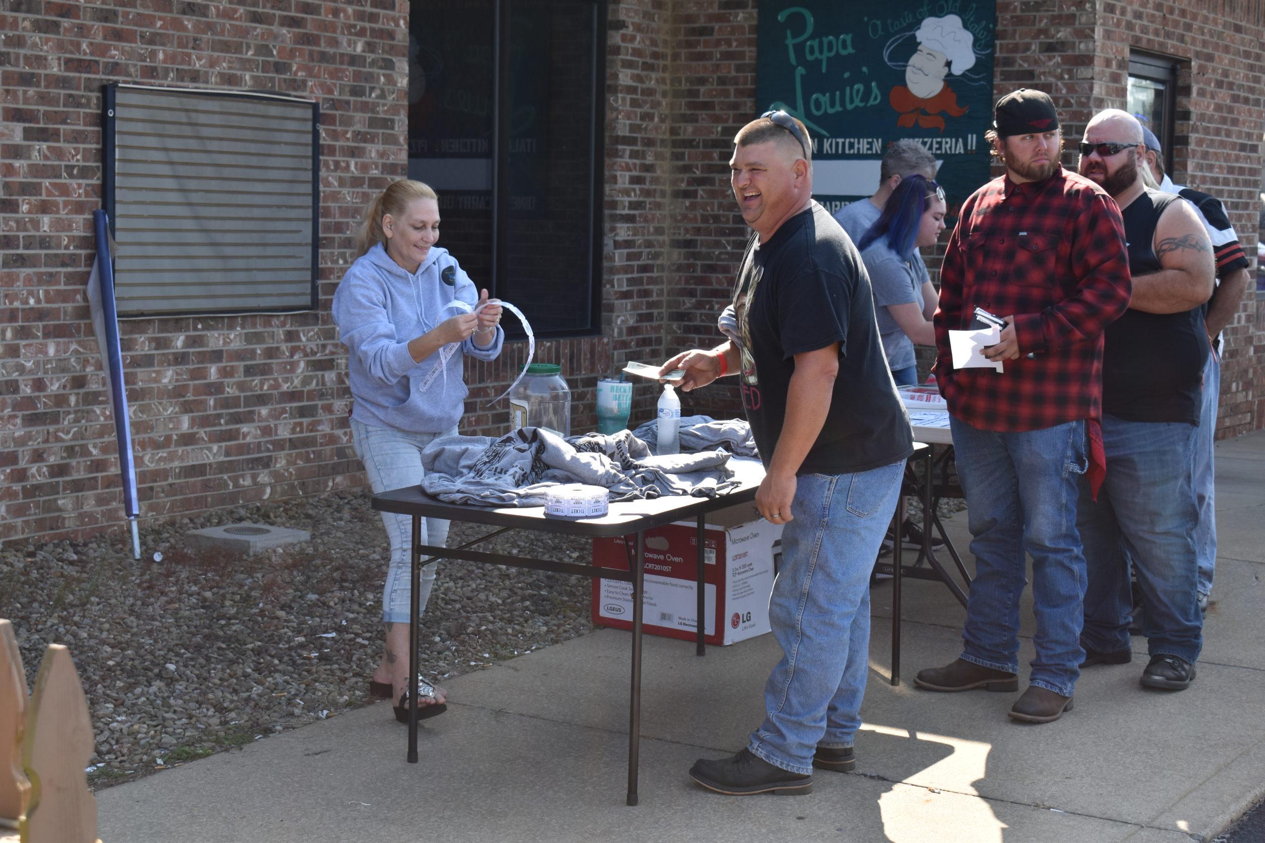 Kimberly King, left, sells raffle tickets.