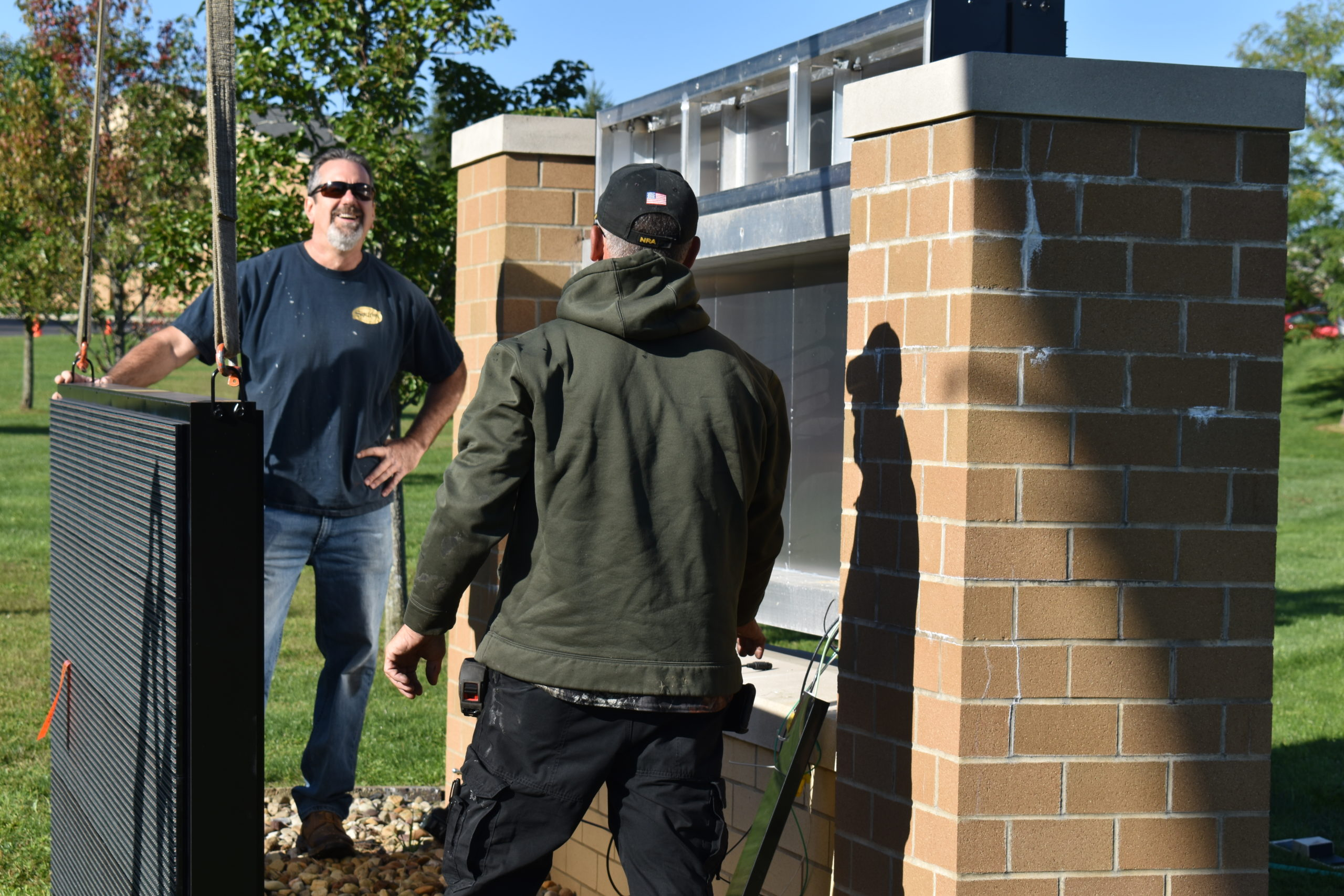 Chuck Kish, left, confers with Rick Madeline of Madeline Sign Lighting as they install the electronic sign at Brookfield schools on Bedford Road.