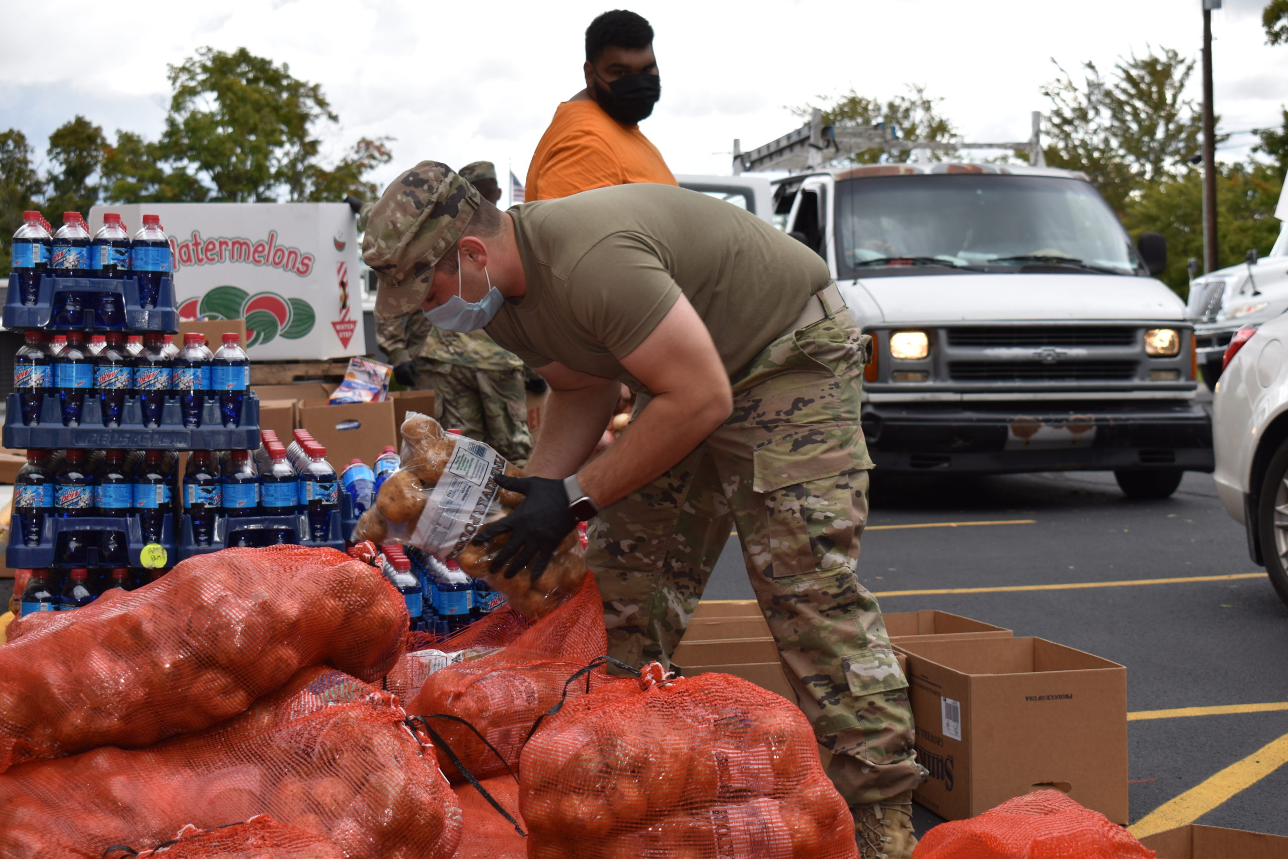 Ohio Army National Guard Sgt. Kyle Kirin grabs a bag of potatoes at a Second Harvest Food Bank of the Mahoning Valley produce giveaway at Brookfield United Methodist Church. Second Harvest employee James Naples is behind him.