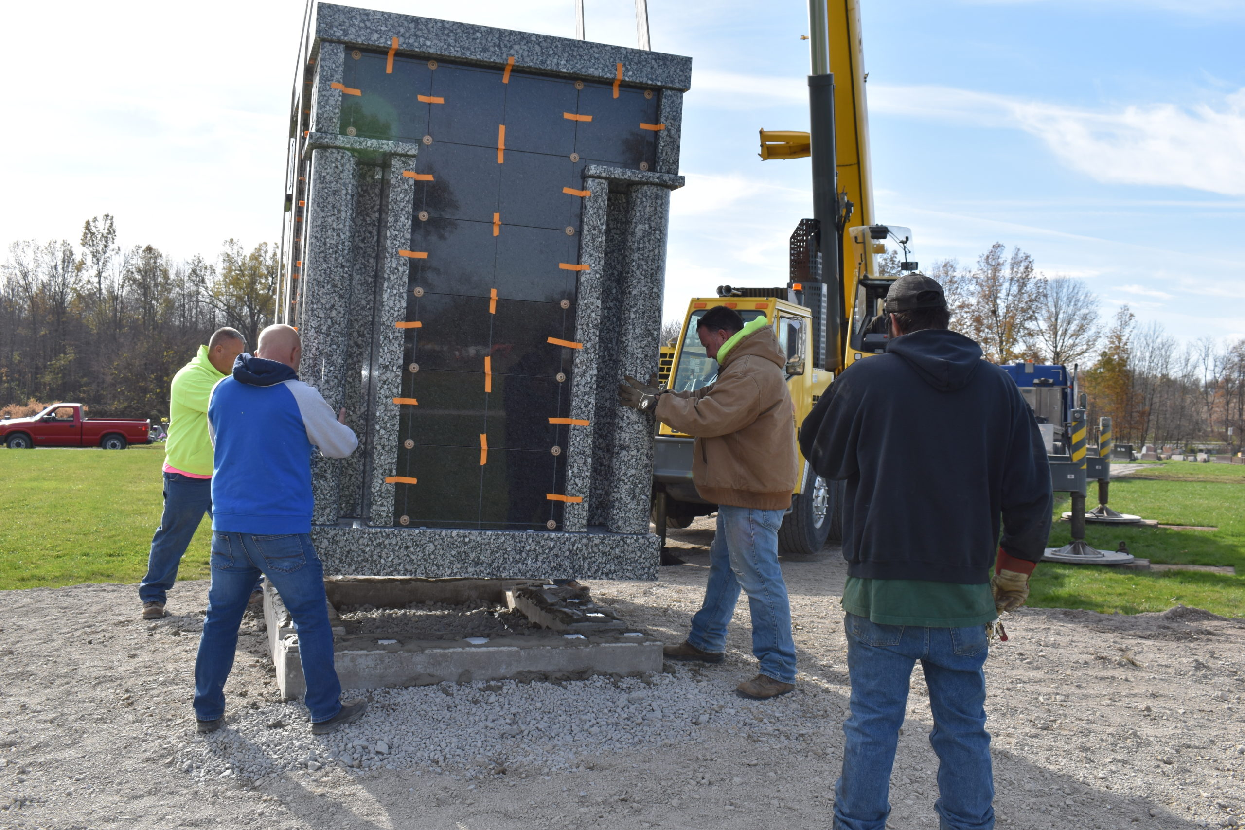 Brookfield road crew members Matt O'Dell, left, and Mark Hughes, second from right, and Jim DeChristefero of Niles Monument position a columbarium as a crane operator with T. Bruce Campbell lowers it onto a pedestal at Brookfield Township Cemetery on Nov. 5.