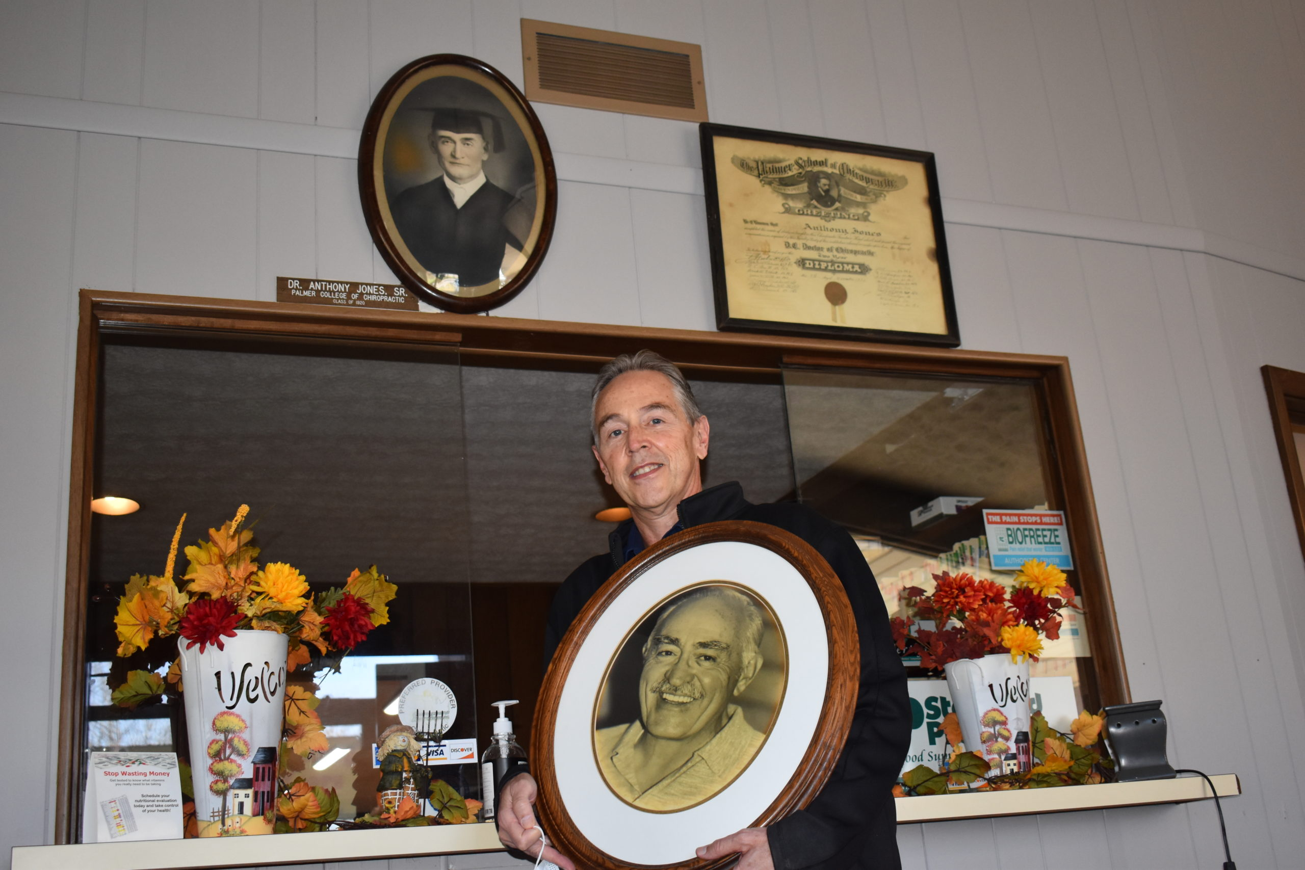 Anthony Jones Jr. holds a photo of his father, Anthony Jones Sr., and they stand below a photo of his grandfather, also named Anthony Jones, who founded Jones Chiropractic Clinic.