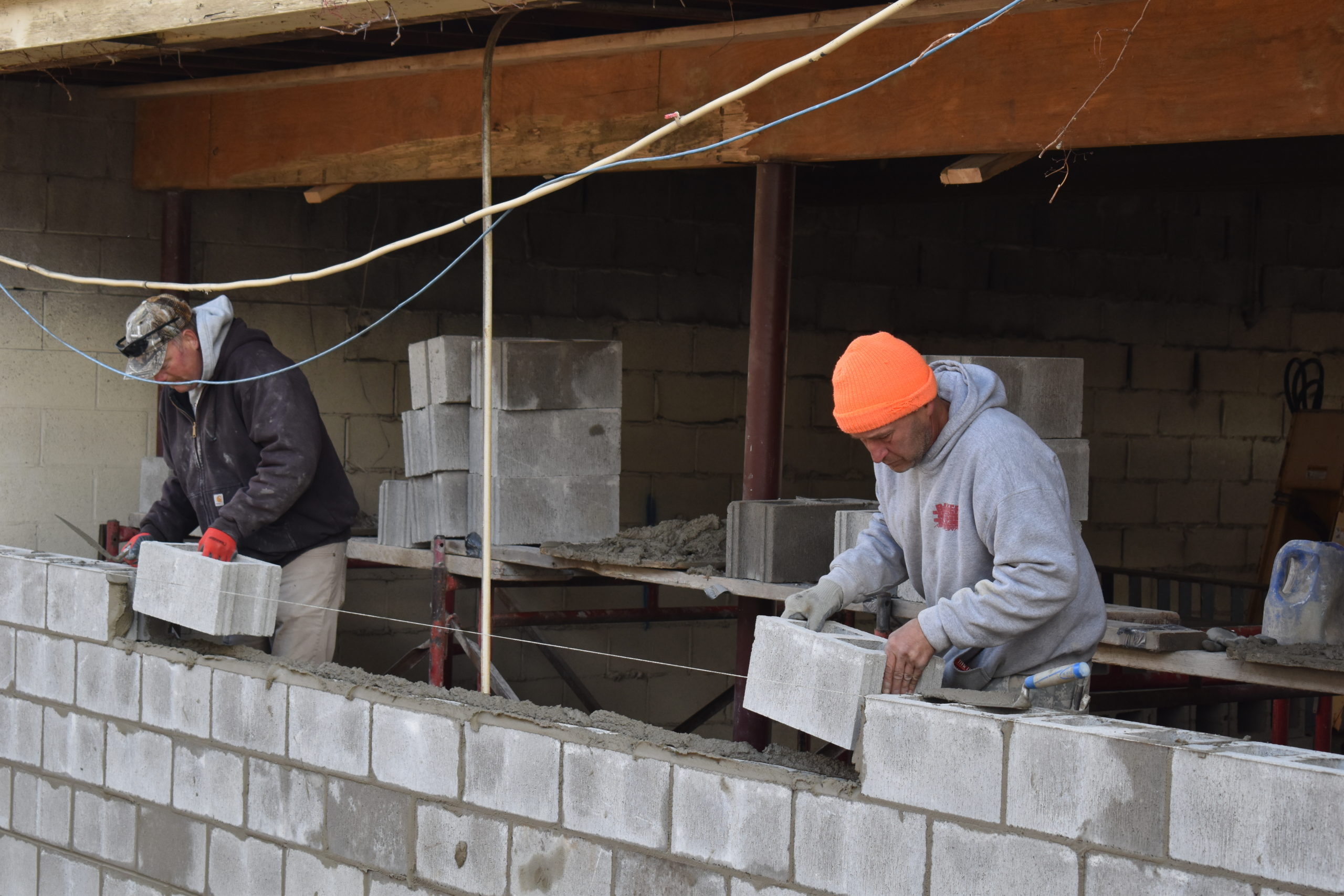 Mike Mayer, left, and Thomas Blazak of Bricklayers and Allied Craft Workers Local #8 of Youngstown rebuild the wall at the Brookfield Local School District bus garage on Grove Street.