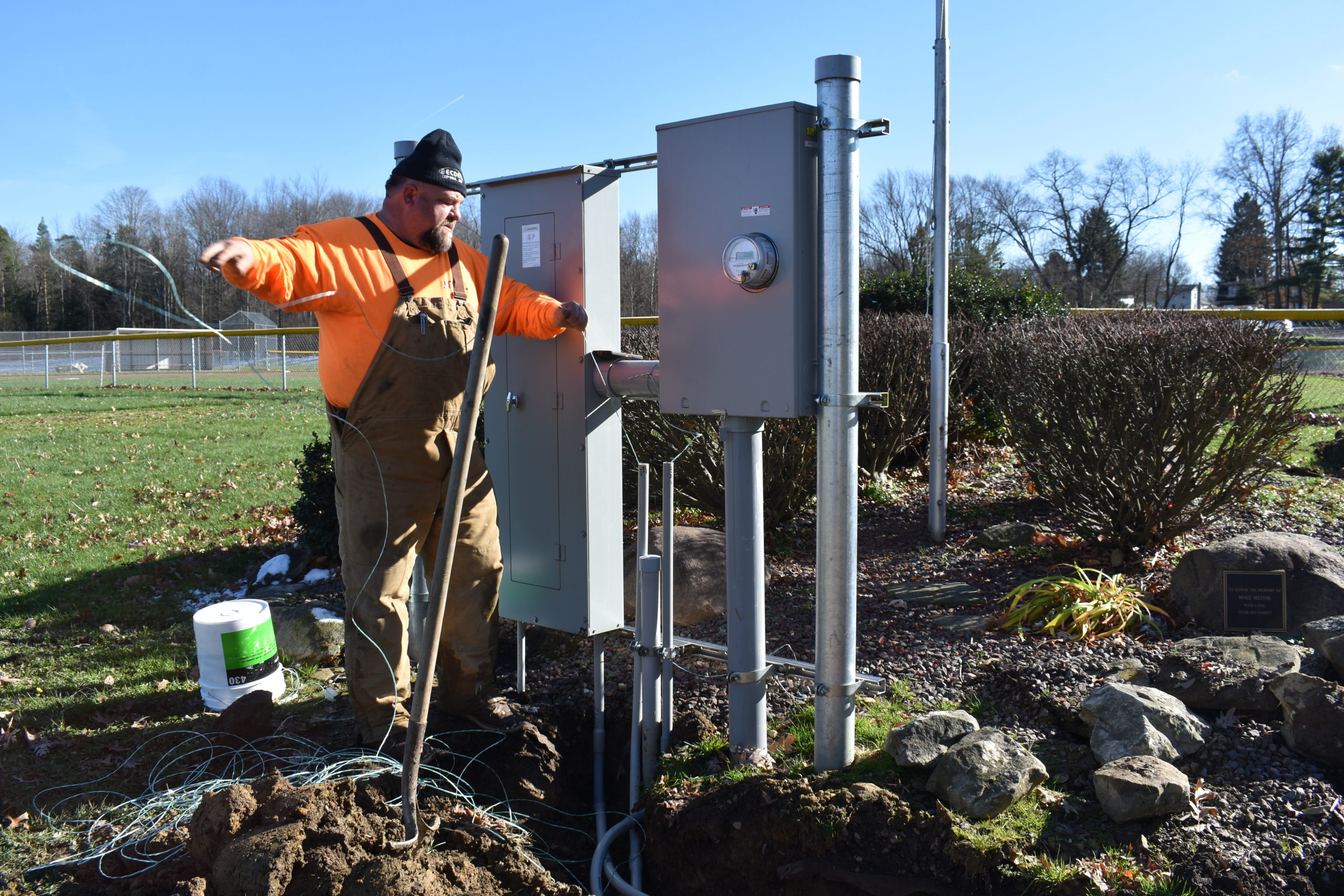 Jack Schell of Becdel Controls pulls wire through a conduit as part of the project to install cameras to monitor social distancing at Brookfield Township Community Park. The project was funded by a CARES Act appropriation.