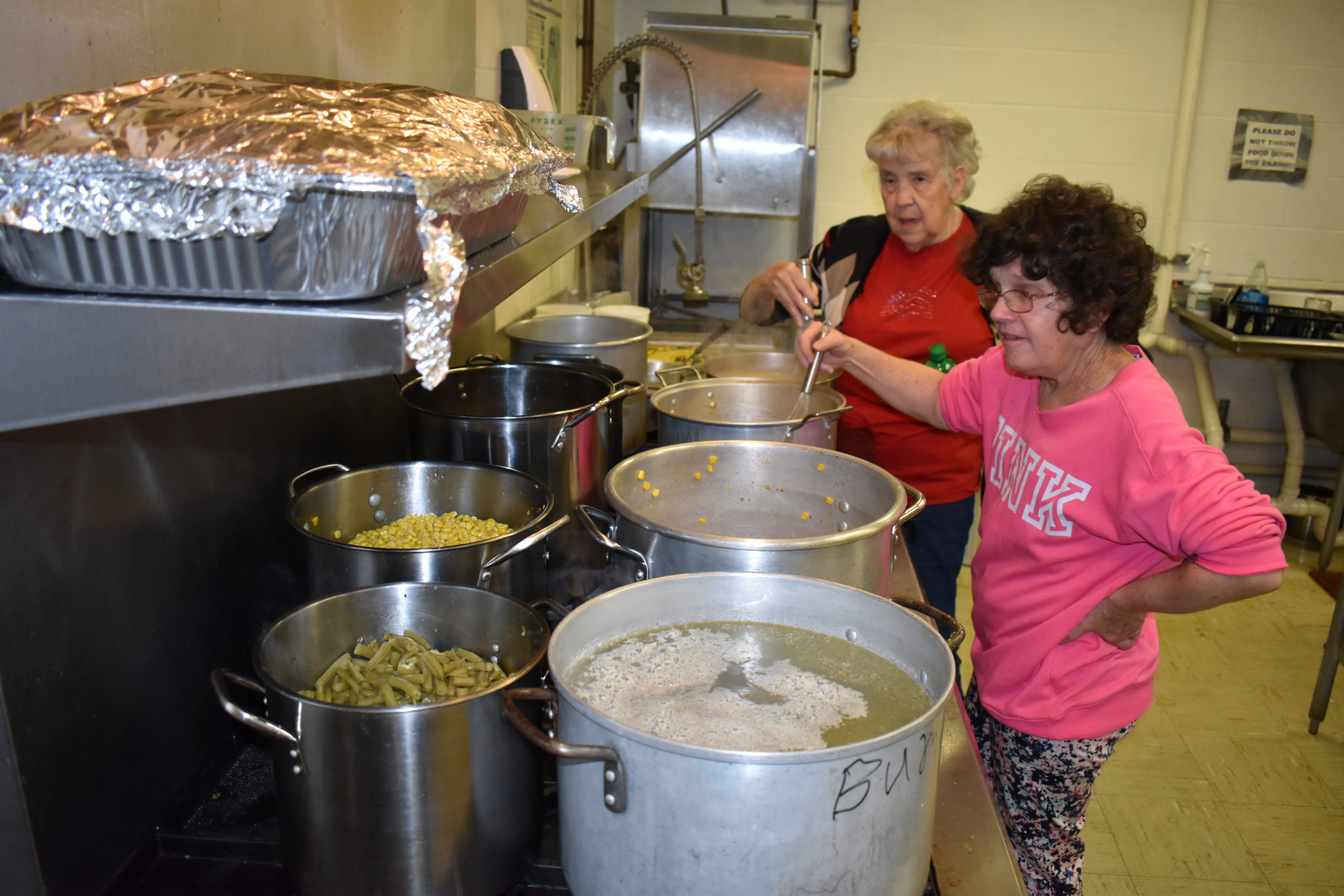 Sue Christman, left, and Janet McMullin work the kitchen at the 2019 Brookfield Township Outreach Association community Thanksgiving dinner.