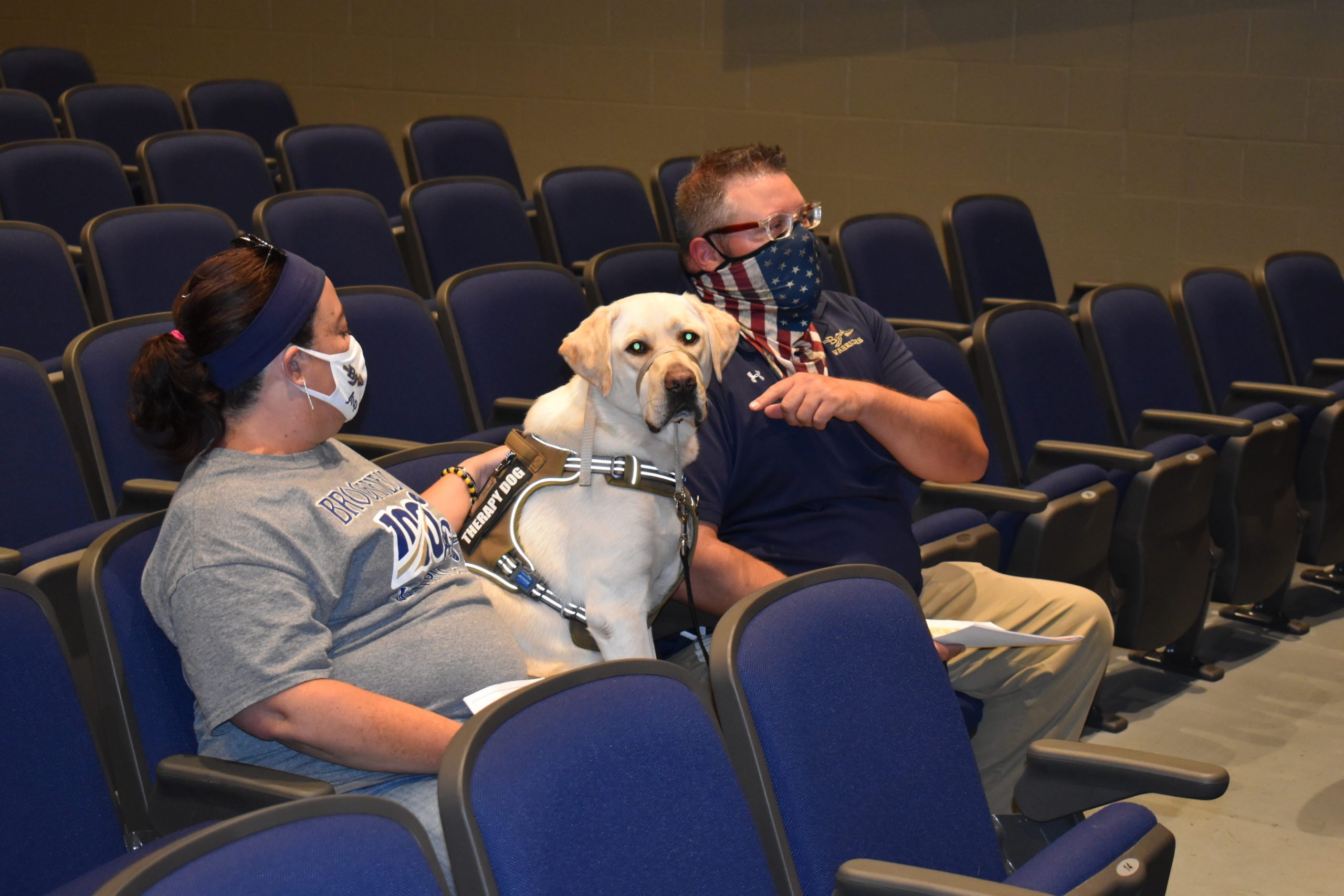 Frankie, a 2-year-old Labrador retriever, sits with teachers Mary Arp and Ken Iser at a Brookfield Board of Education meeting.